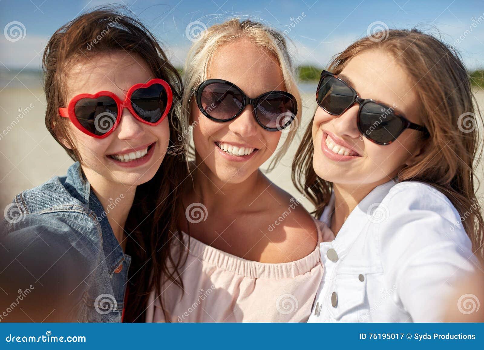 Grupo de mulheres de sorriso que tomam o selfie na praia