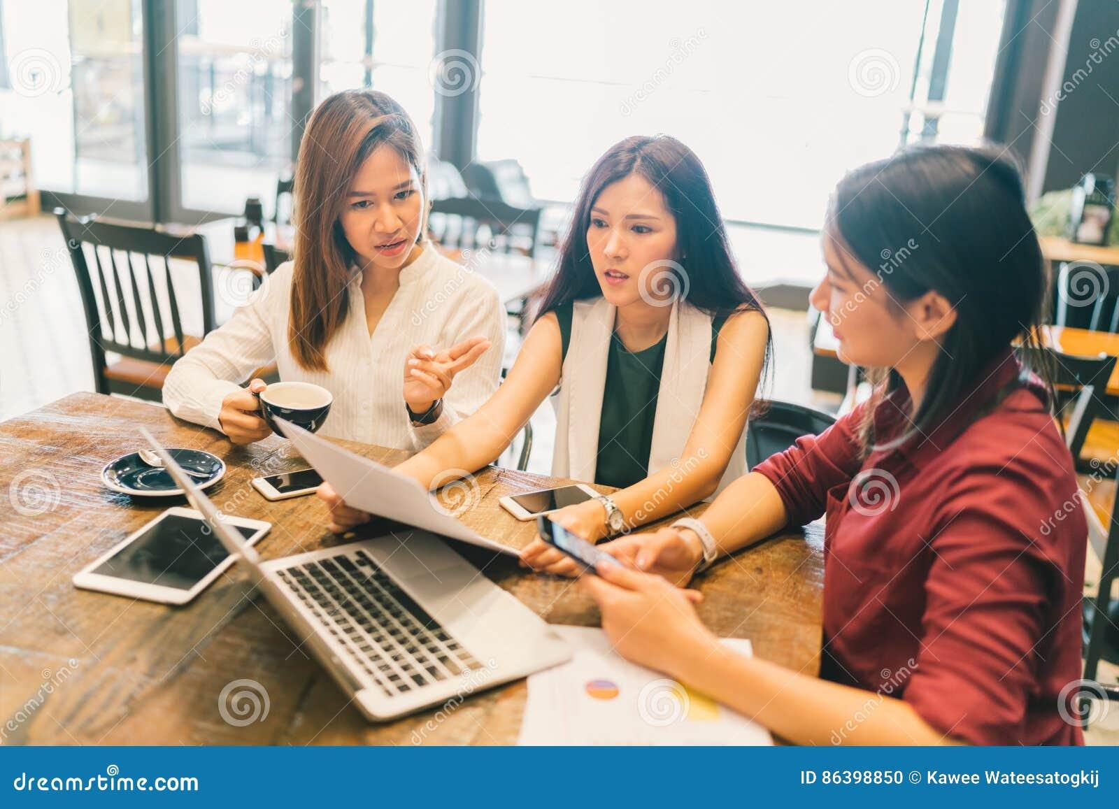 Grupo de mulheres ou de estudantes universitário asiáticas novas na discussão séria do clique da reunião de negócios ou do projet