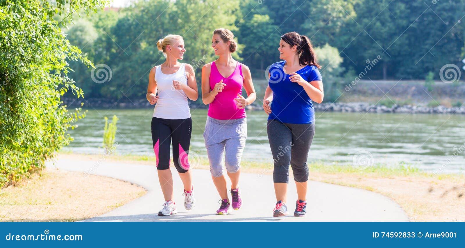 Grupo de mulheres que correm em movimentar-se da beira do lago