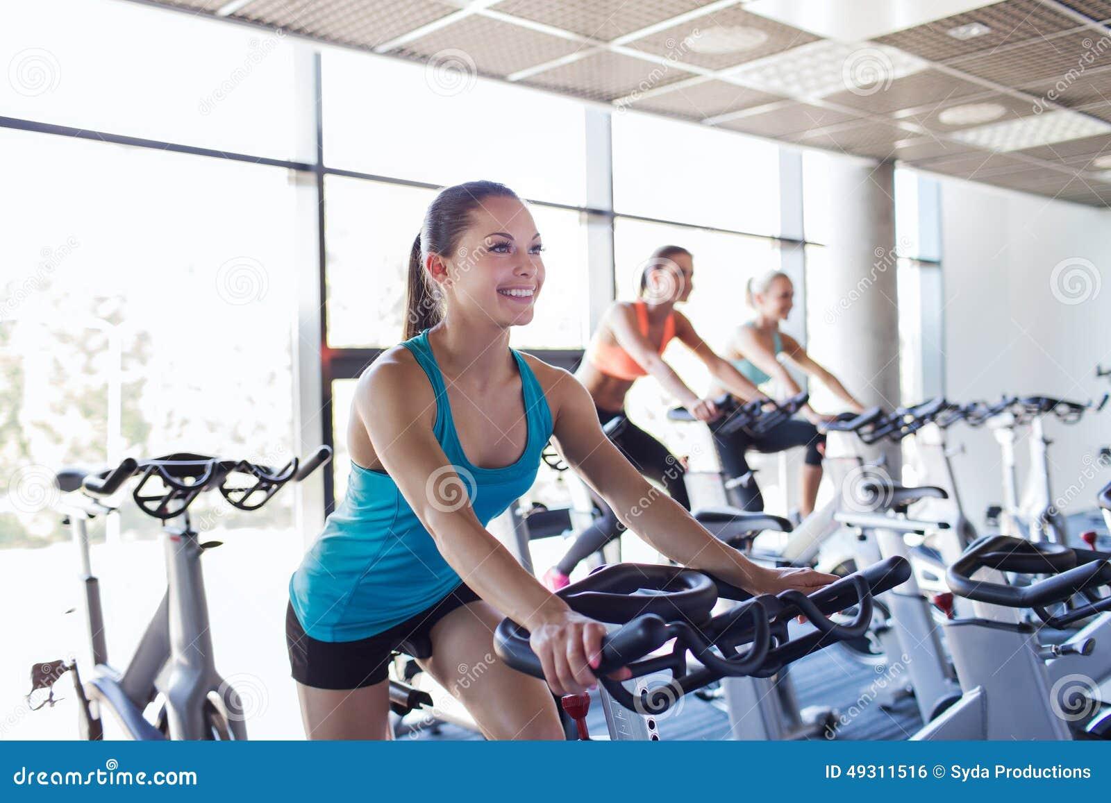Grupo de mulheres que montam na bicicleta de exercício no gym