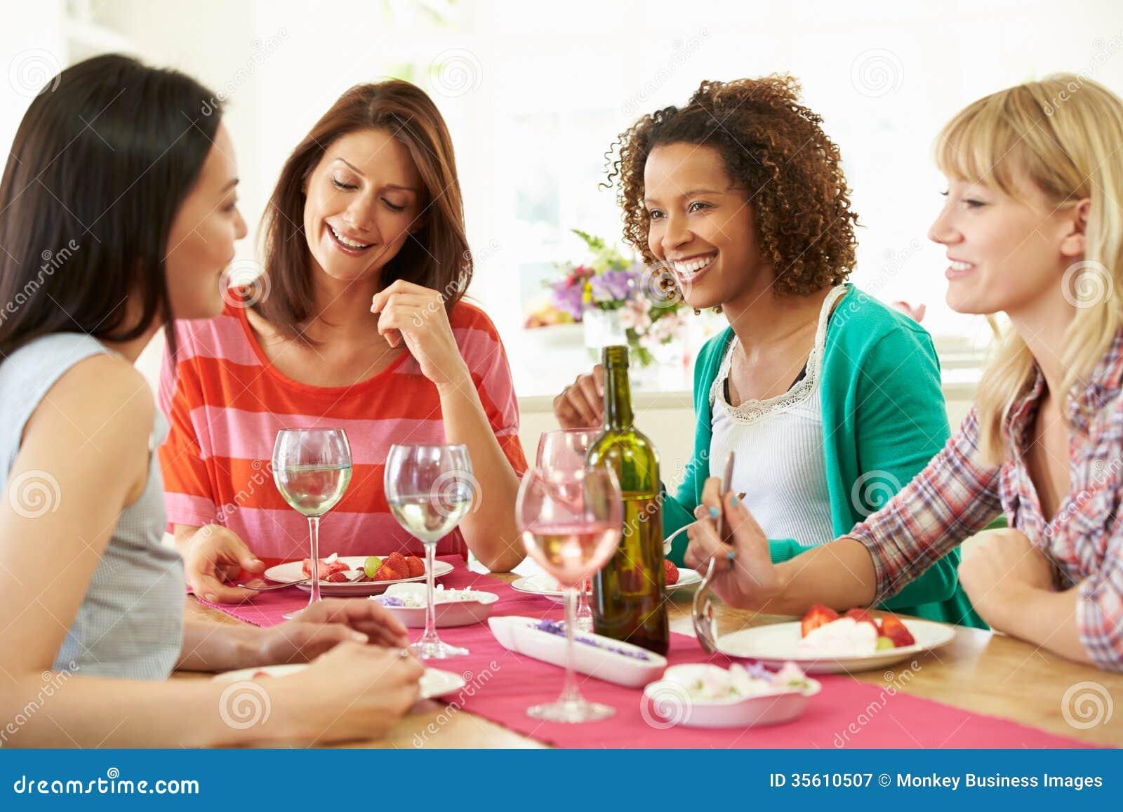 Grupo de mulheres que sentam-se em torno da tabela que come a sobremesa