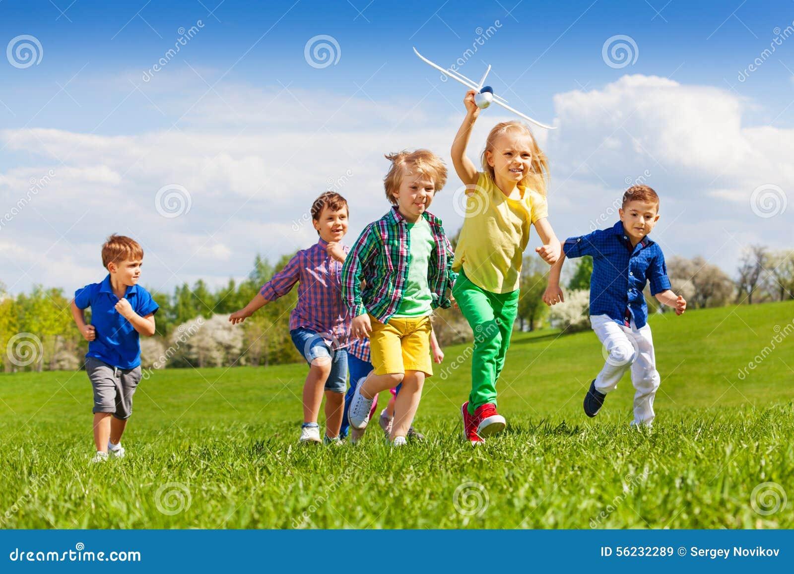 Grupo de niños corrientes felices con el aeroplano blanco