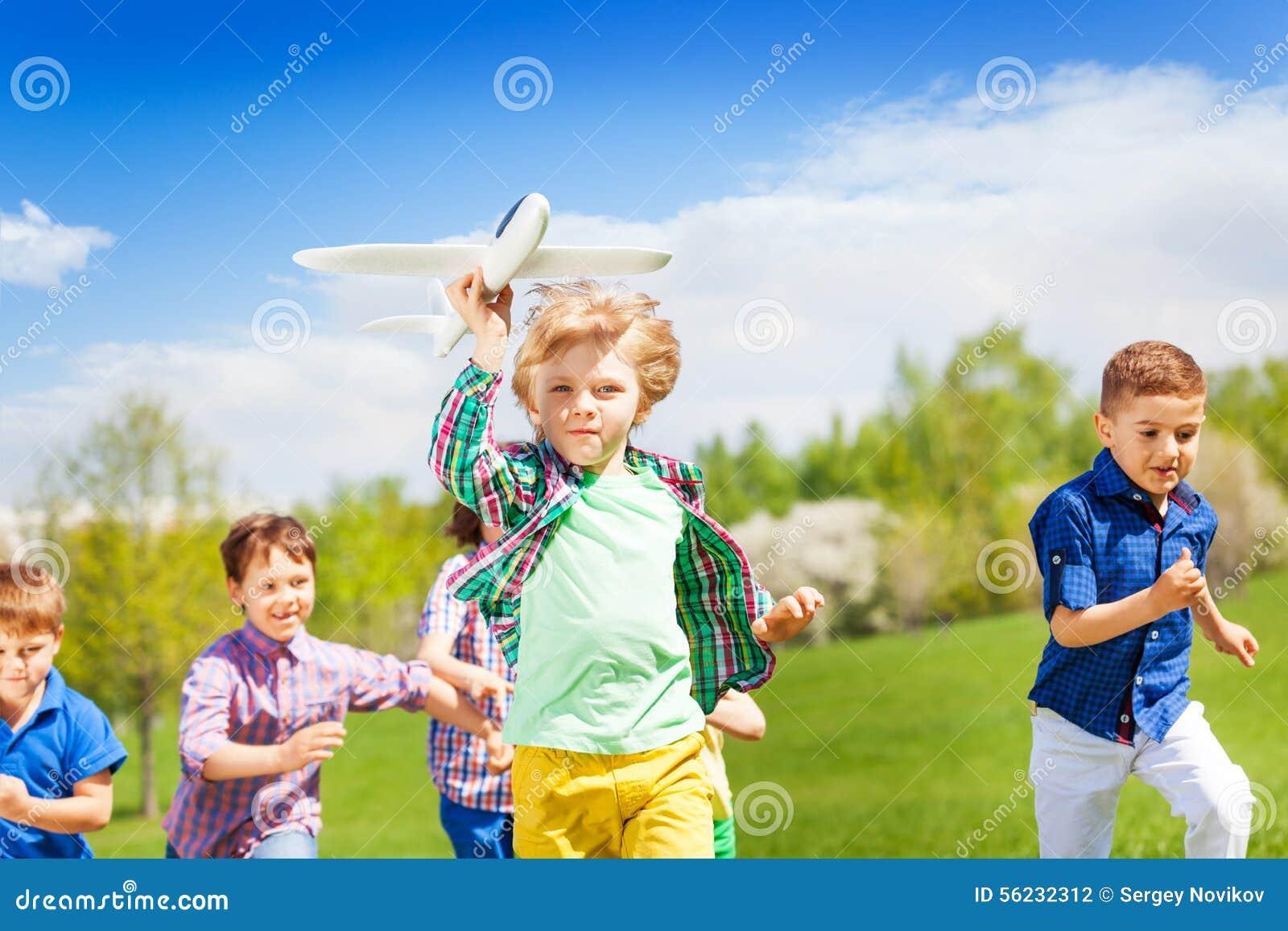Grupo de niños corrientes felices con el juguete del aeroplano