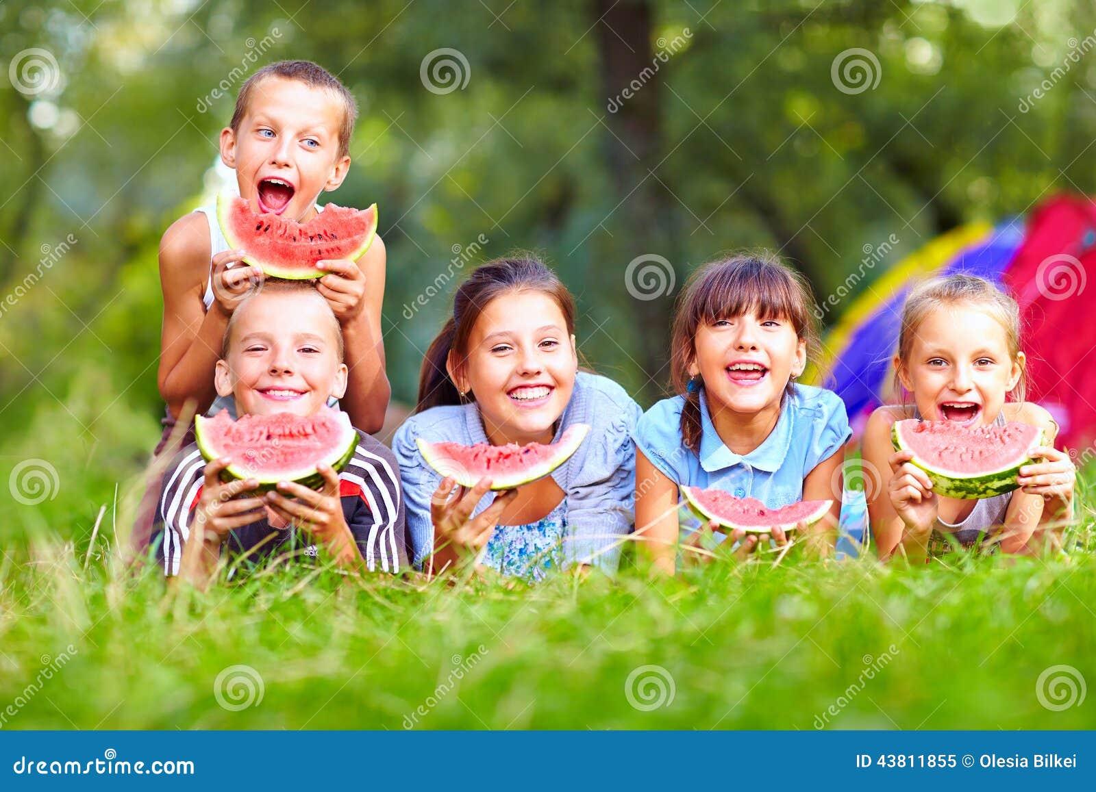 Grupo de niños felices que comen las sandías