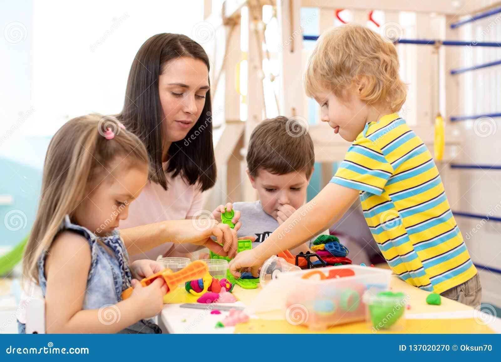 Grupo de niños de la guardería que juegan con plasticine o pasta Los niños se divierten así como el modelado colorido