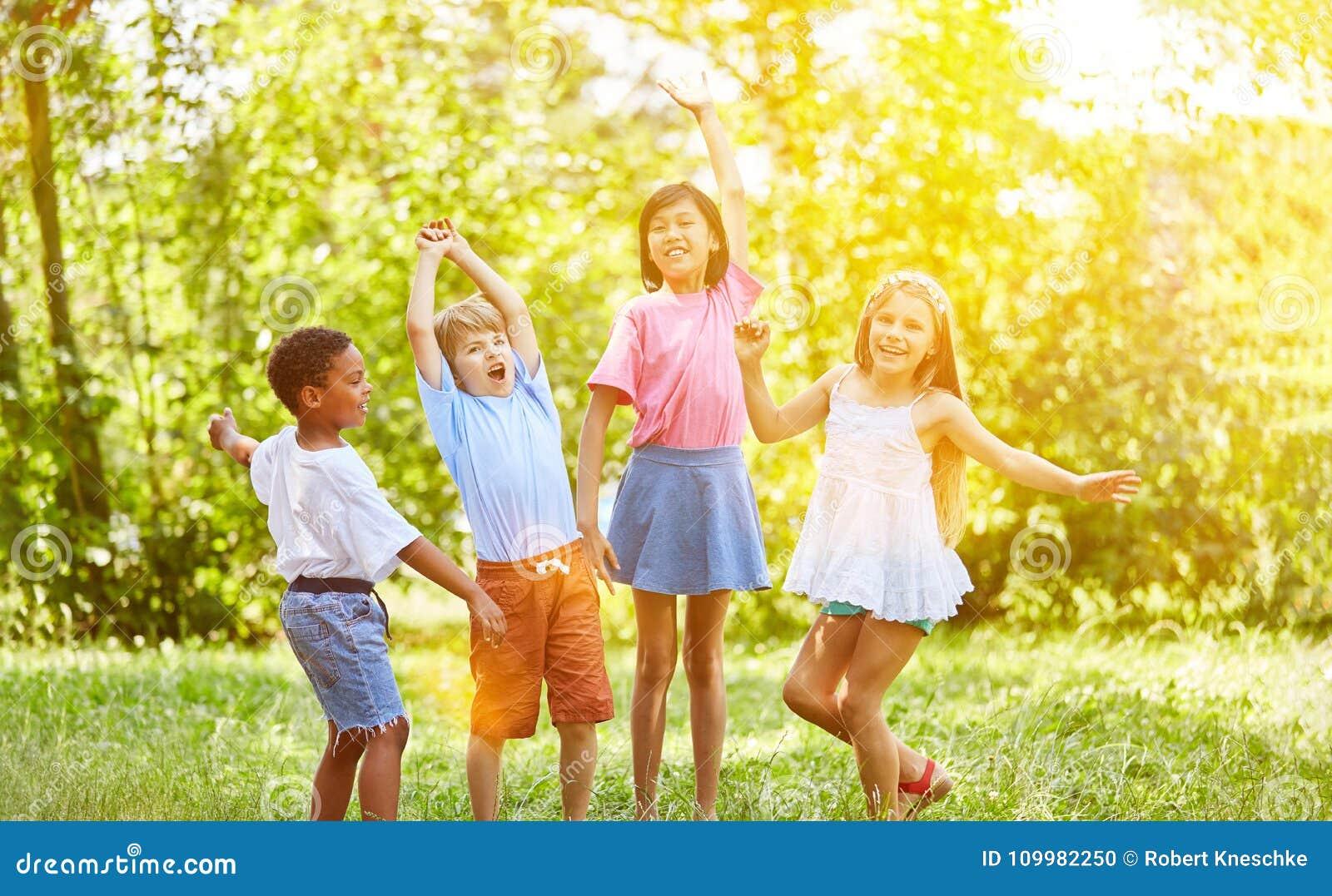 Grupo de niños que animan y que bailan en verano