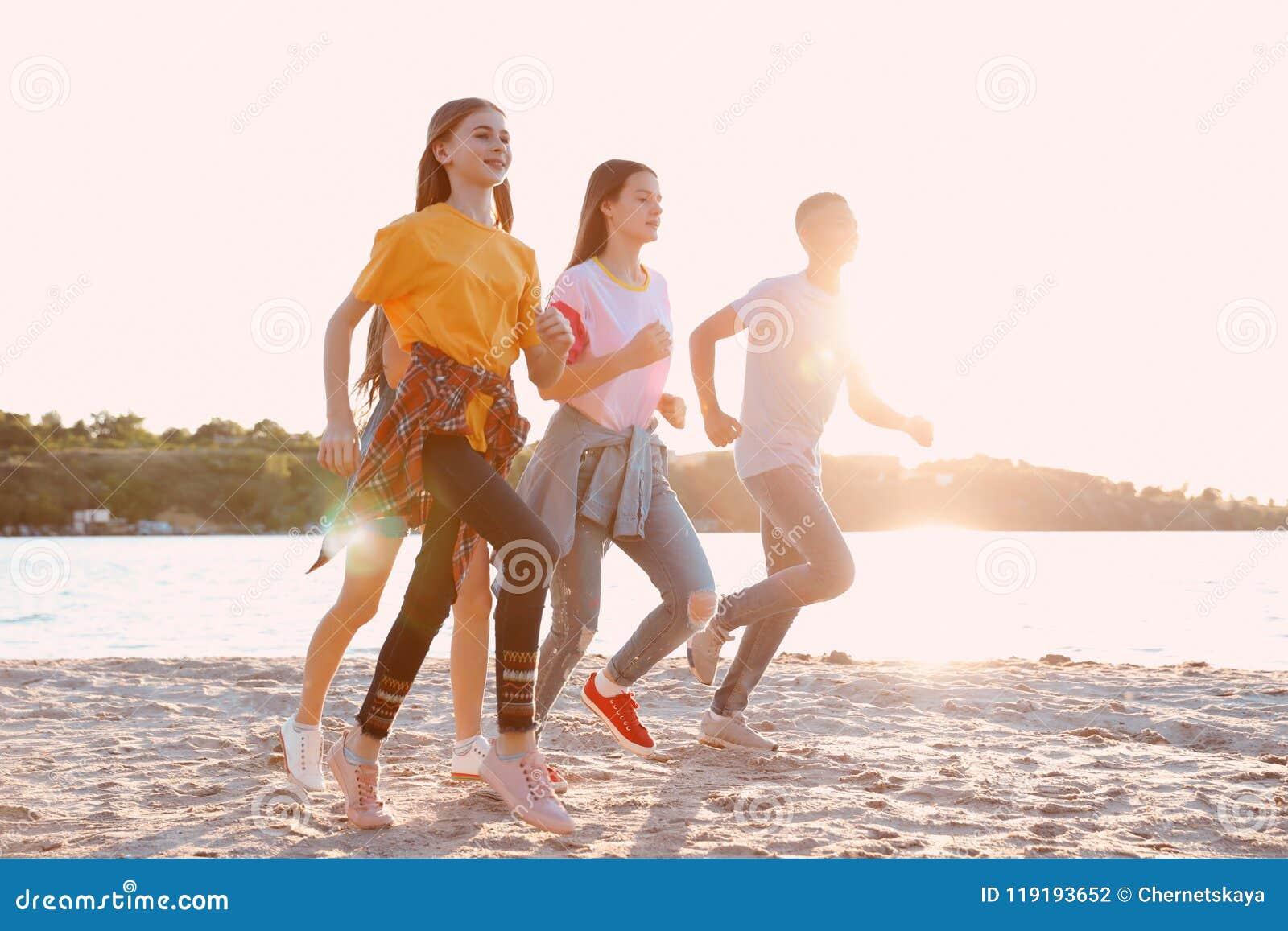 Grupo de niños que corren en la playa Campamento de verano