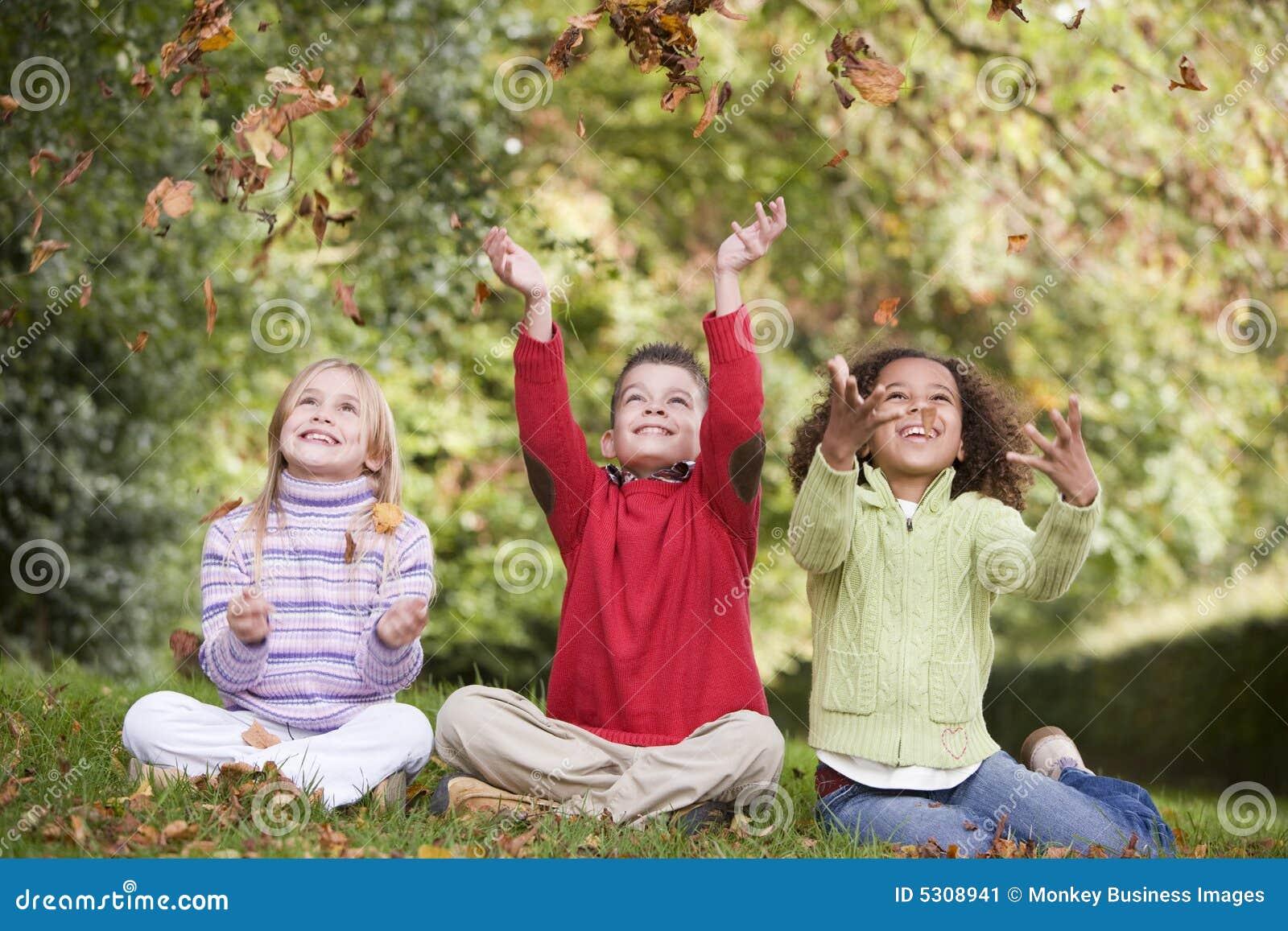 Grupo de niños que juegan en hojas de otoño