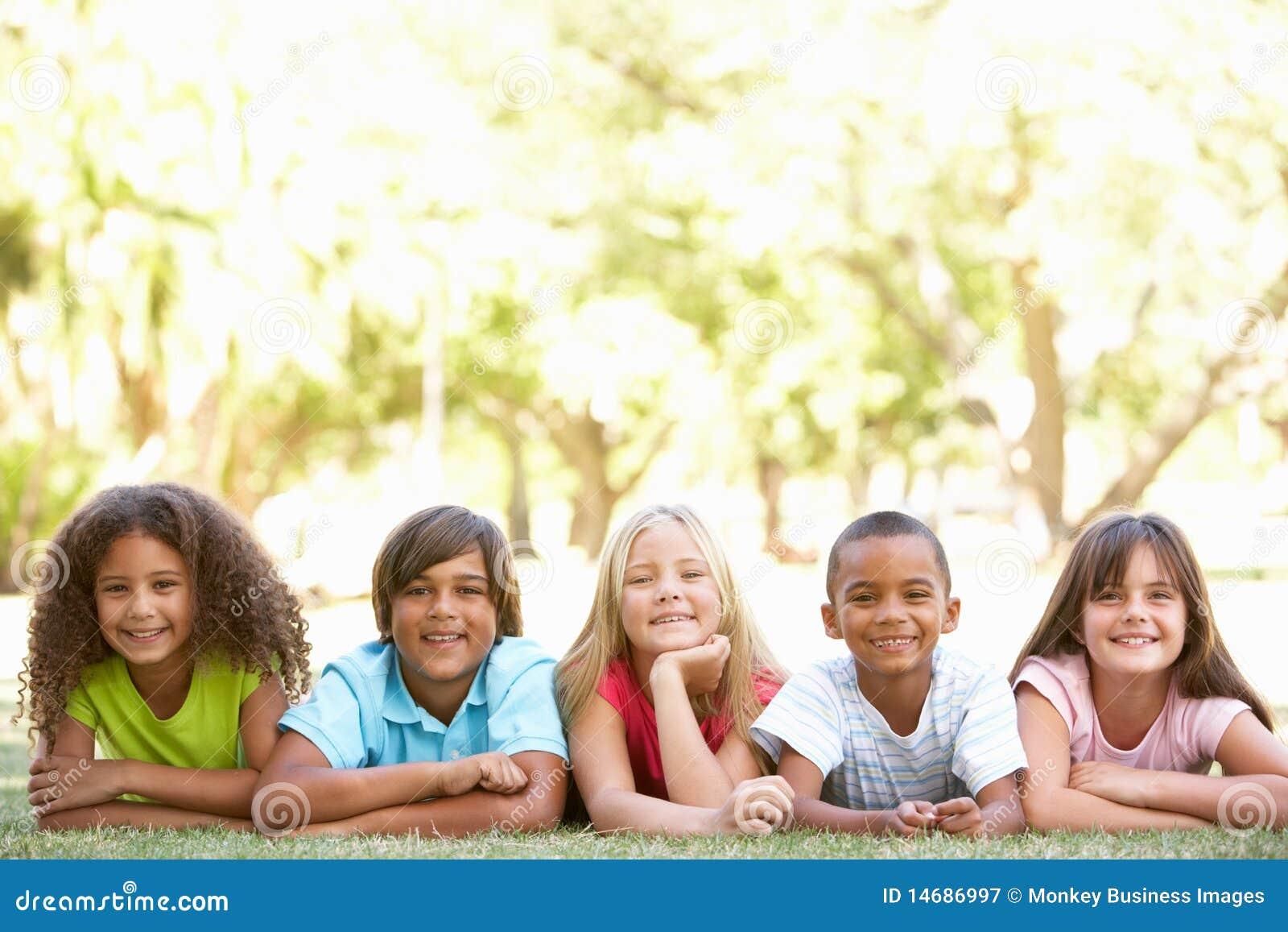 Grupo de niños que mienten en los estómagos en parque