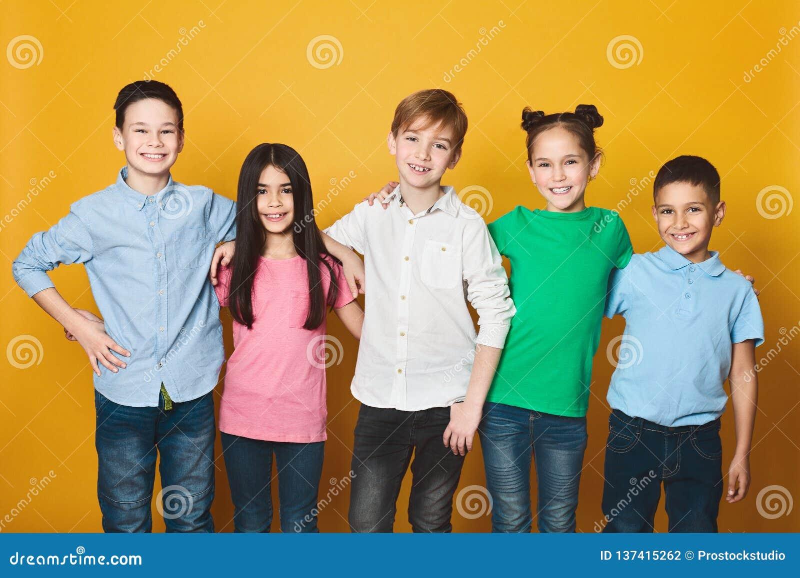 Grupo de niños que se colocan en fila, mirando la cámara