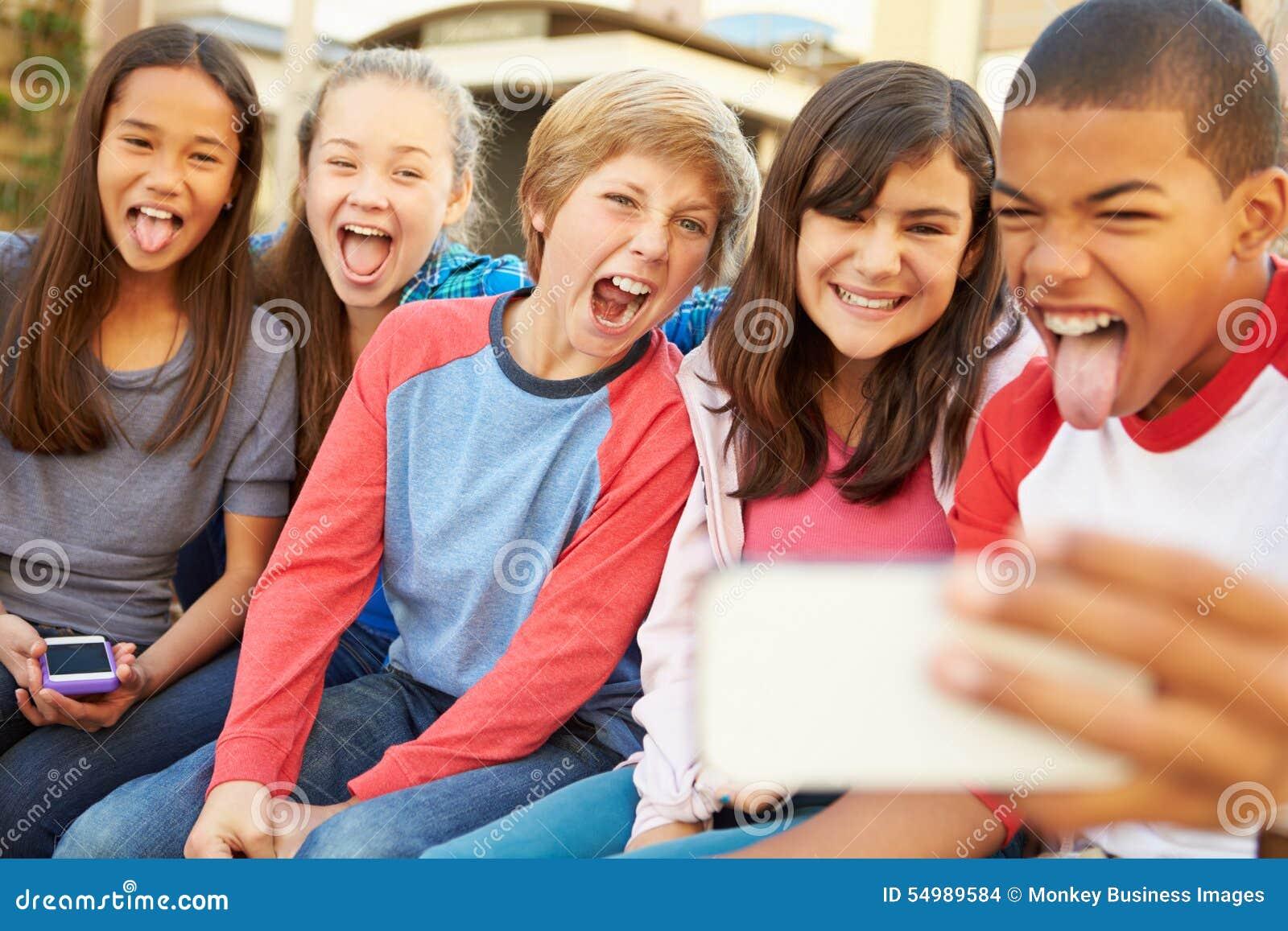 Grupo de niños que se sientan en banco en la alameda que toma Selfie