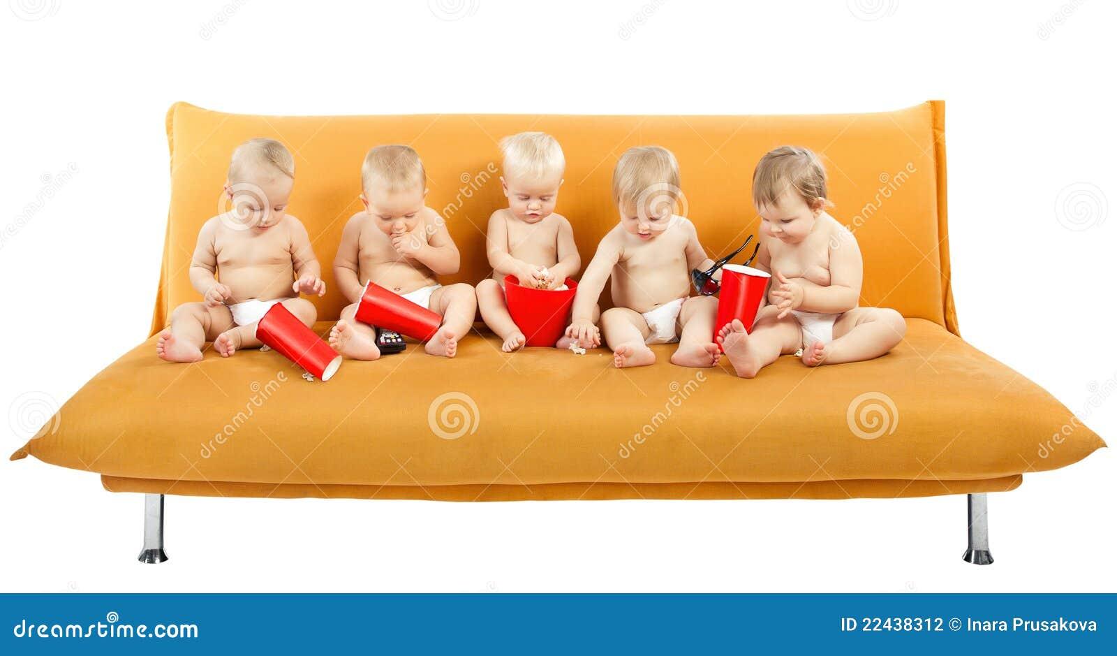 Grupo de niños que se sientan en el sofá, comiendo las palomitas