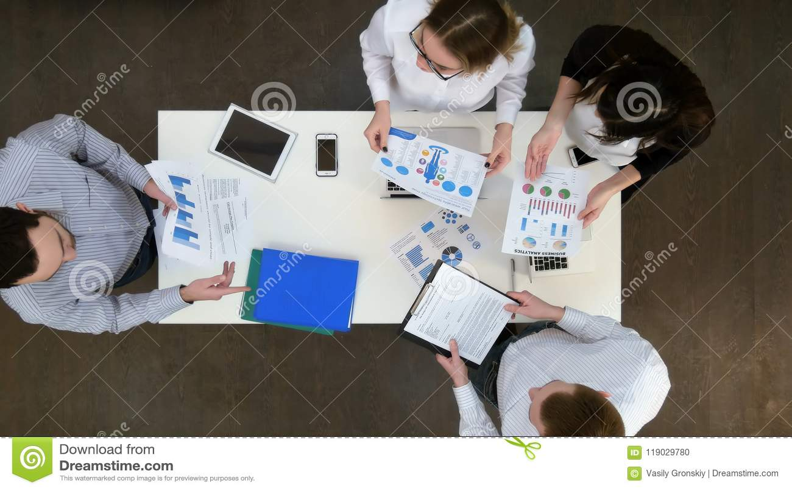 Grupo de oficinistas que discuten diagramas y gráficos del negocio