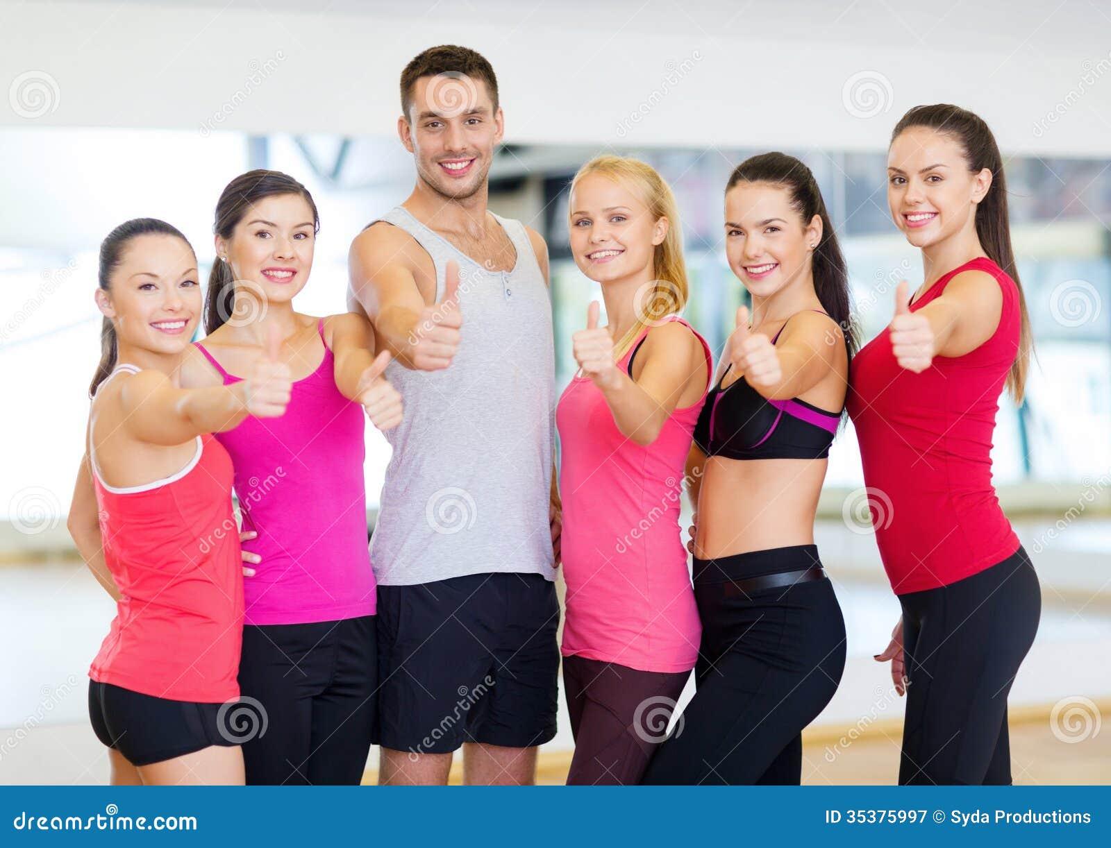 Grupo de personas en el gimnasio que muestra los pulgares for El gimnasio es un deporte