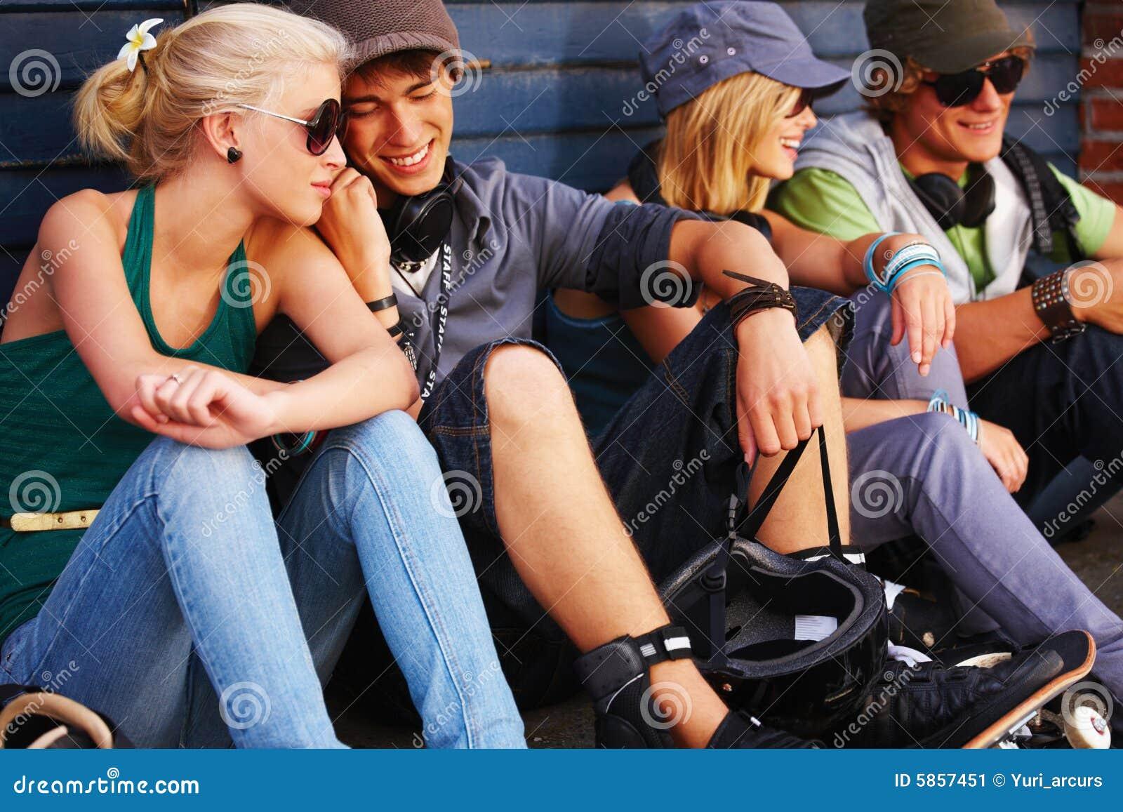 Grupo de personas joven que se sienta junto divirtiéndose