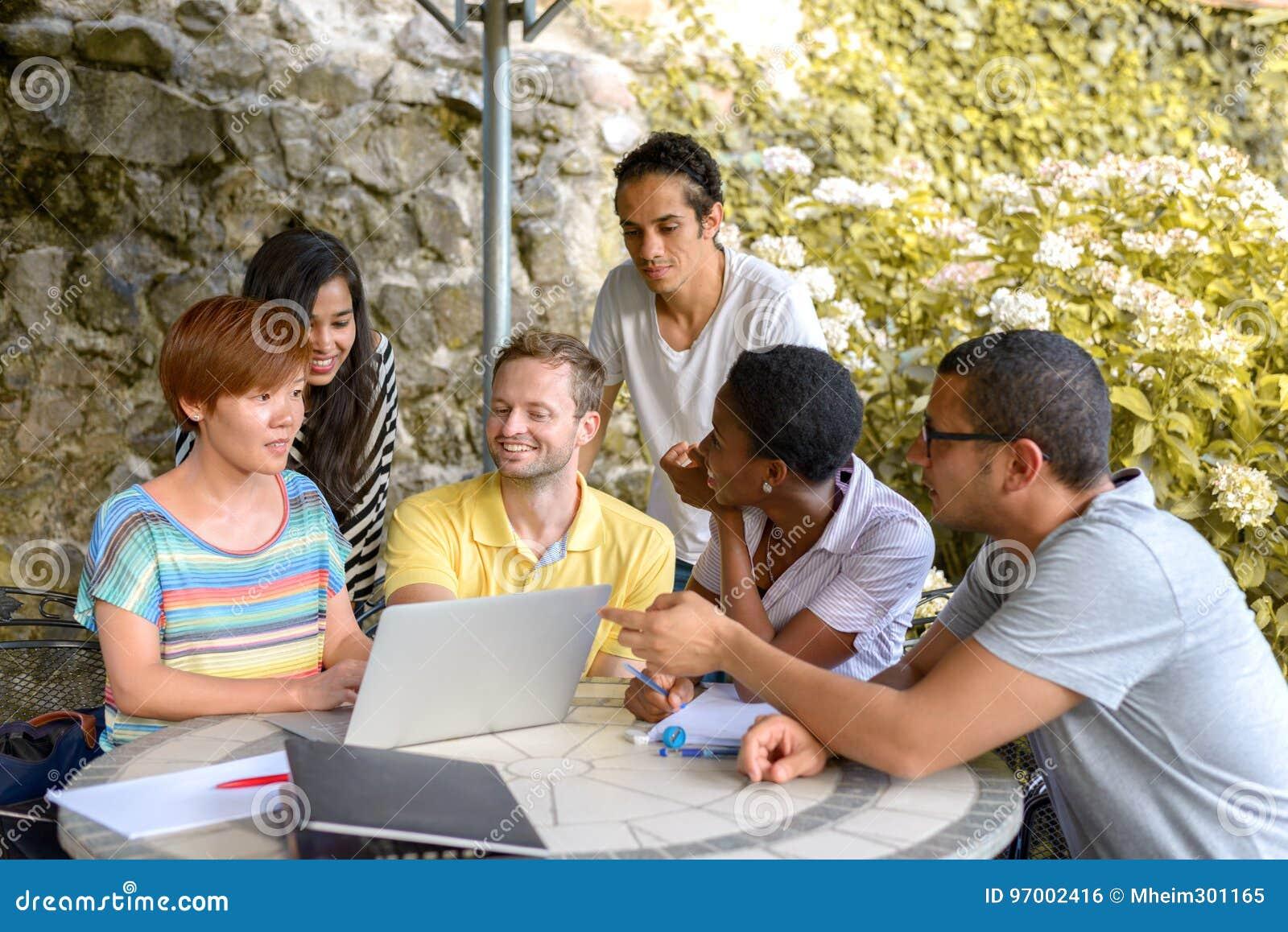 Grupo de personas multicultural que discute por el ordenador portátil