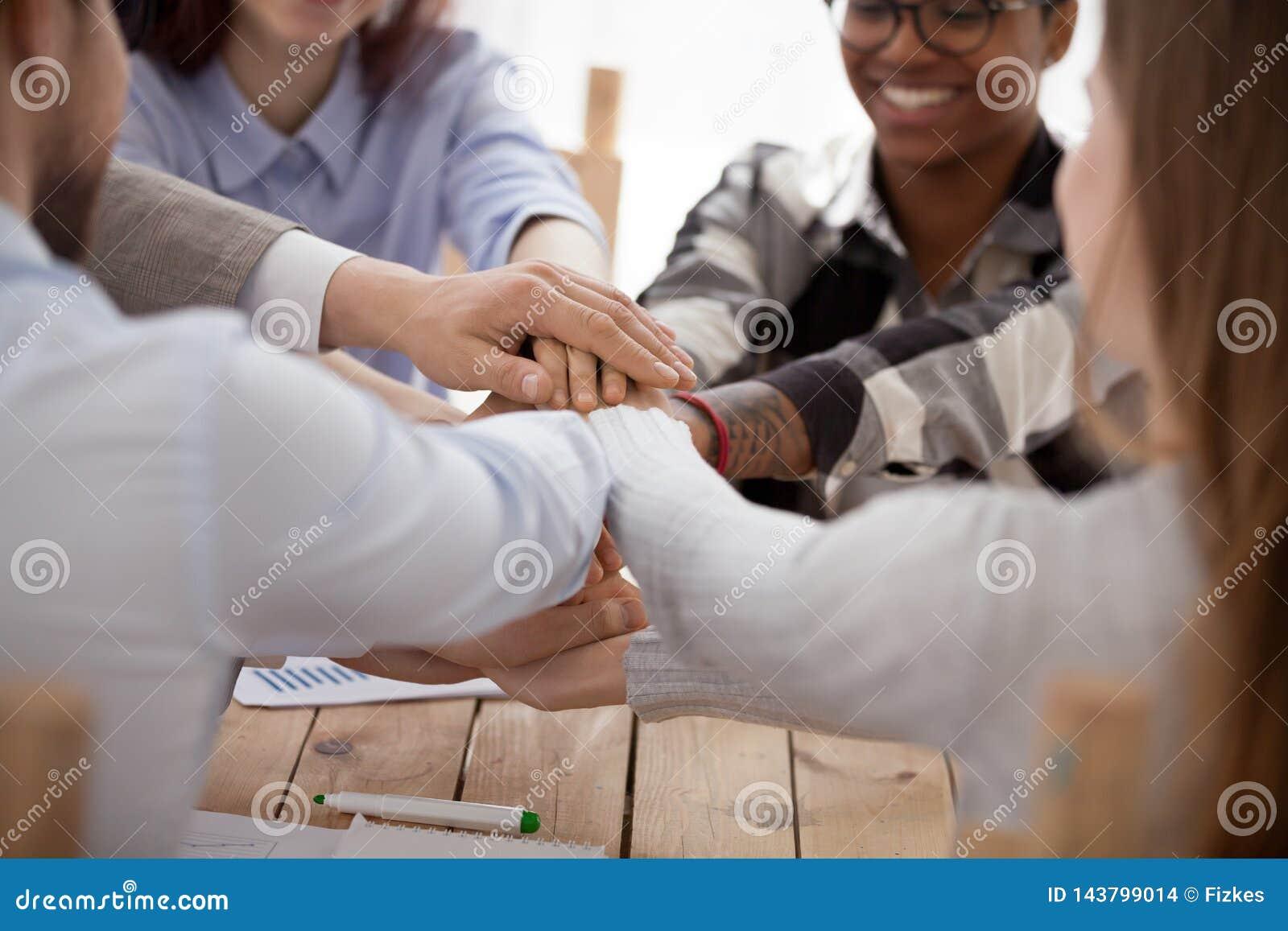 Grupo de personas que apila las manos que se sientan en oficina junto
