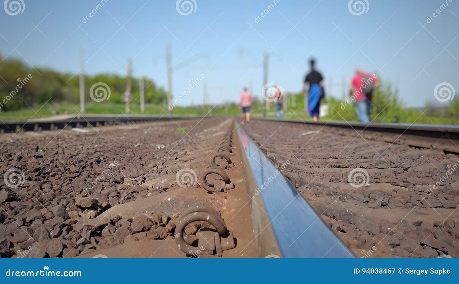 Grupo de personas que camina a lo largo de las pistas ferroviarias