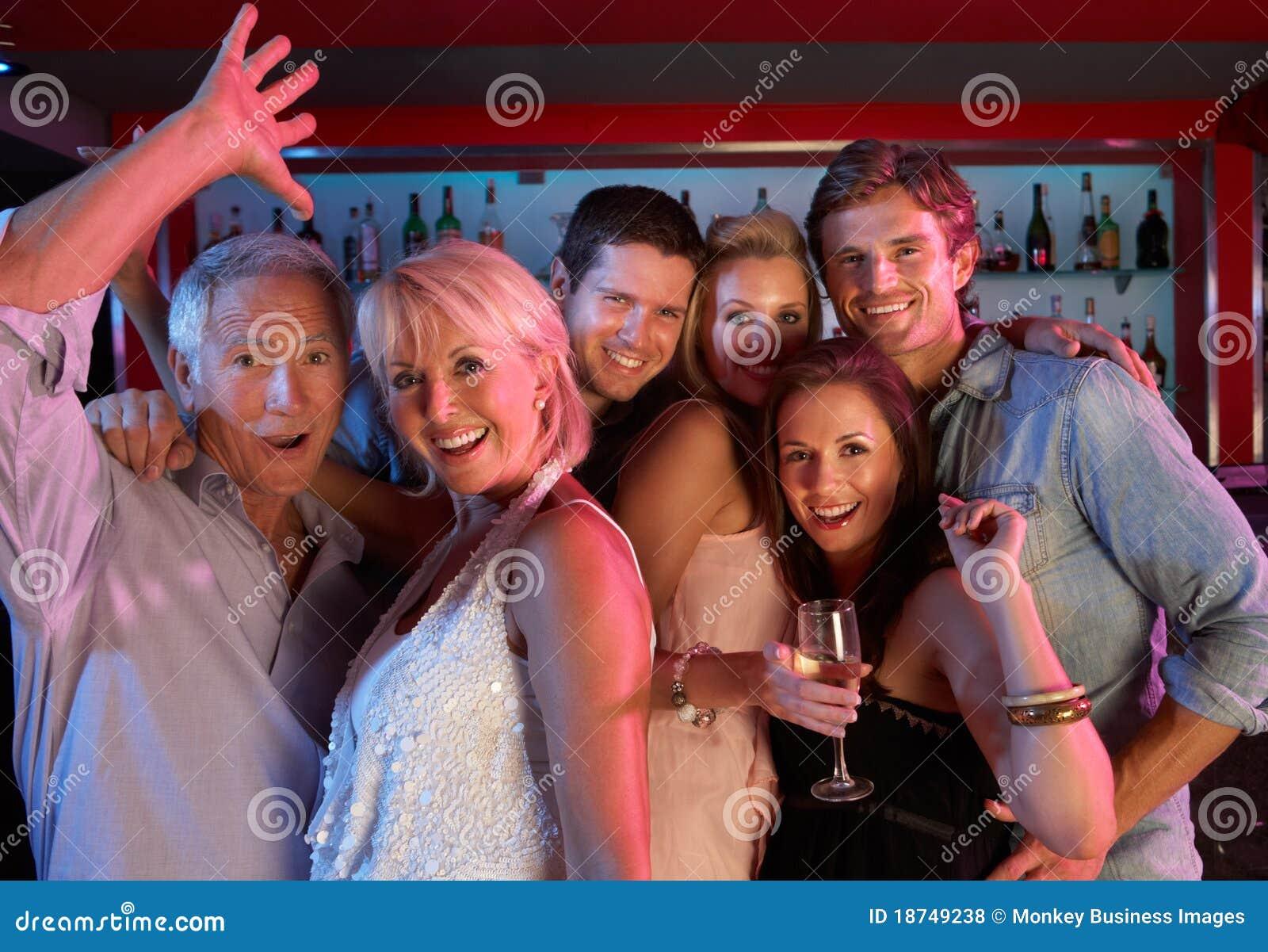 Grupo de personas que se divierte en barra ocupada