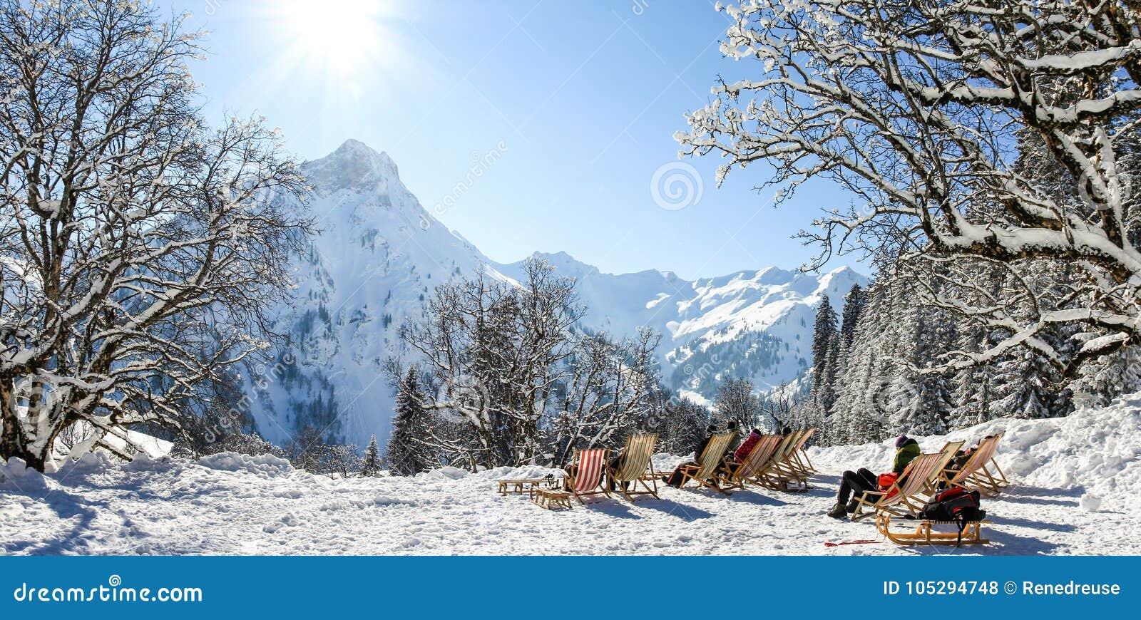 Grupo de personas que se sienta con las sillas de cubierta en montañas del invierno El tomar el sol en nieve Alemania, Baviera, A
