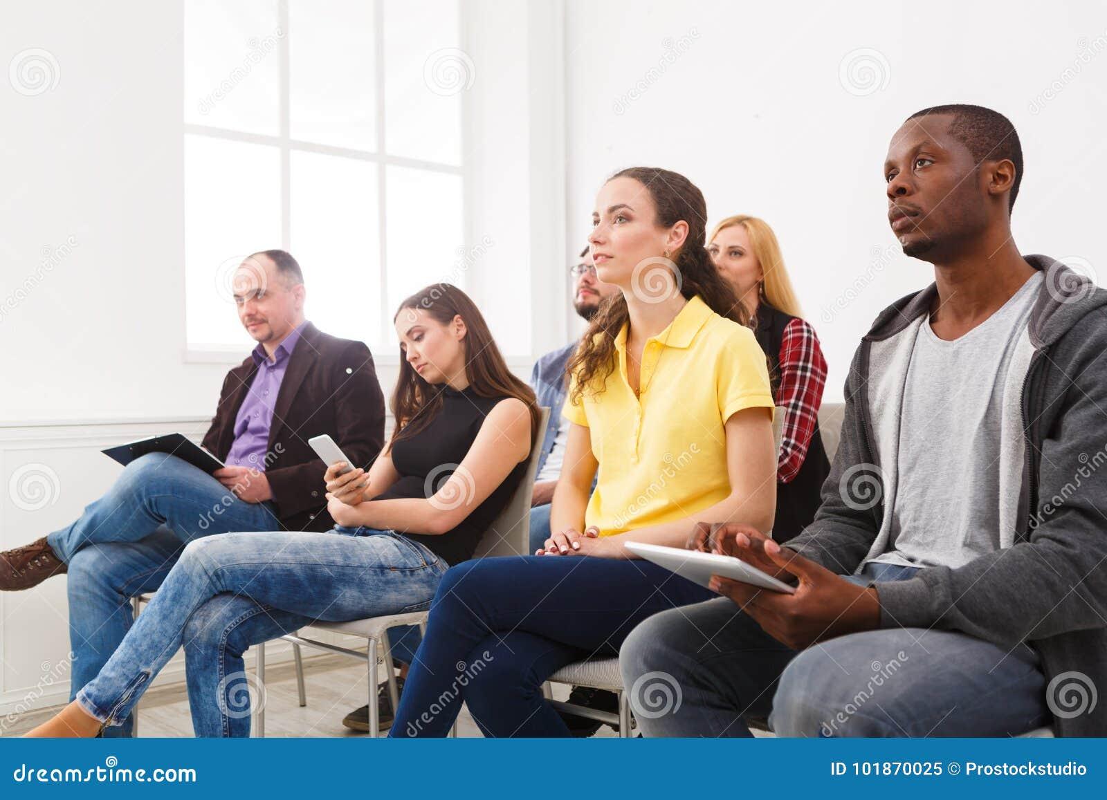 Grupo de personas que se sienta en el seminario, espacio de la copia
