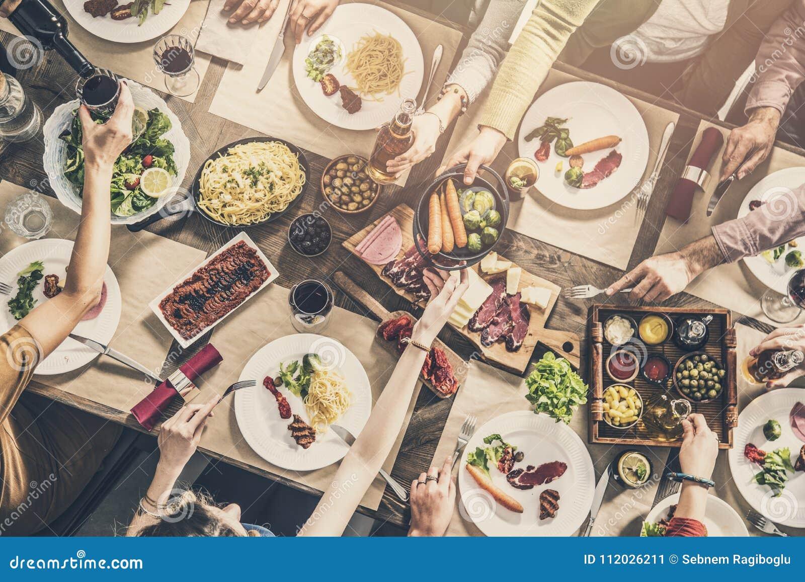 Grupo de personas que tiene cena de la unidad de la comida