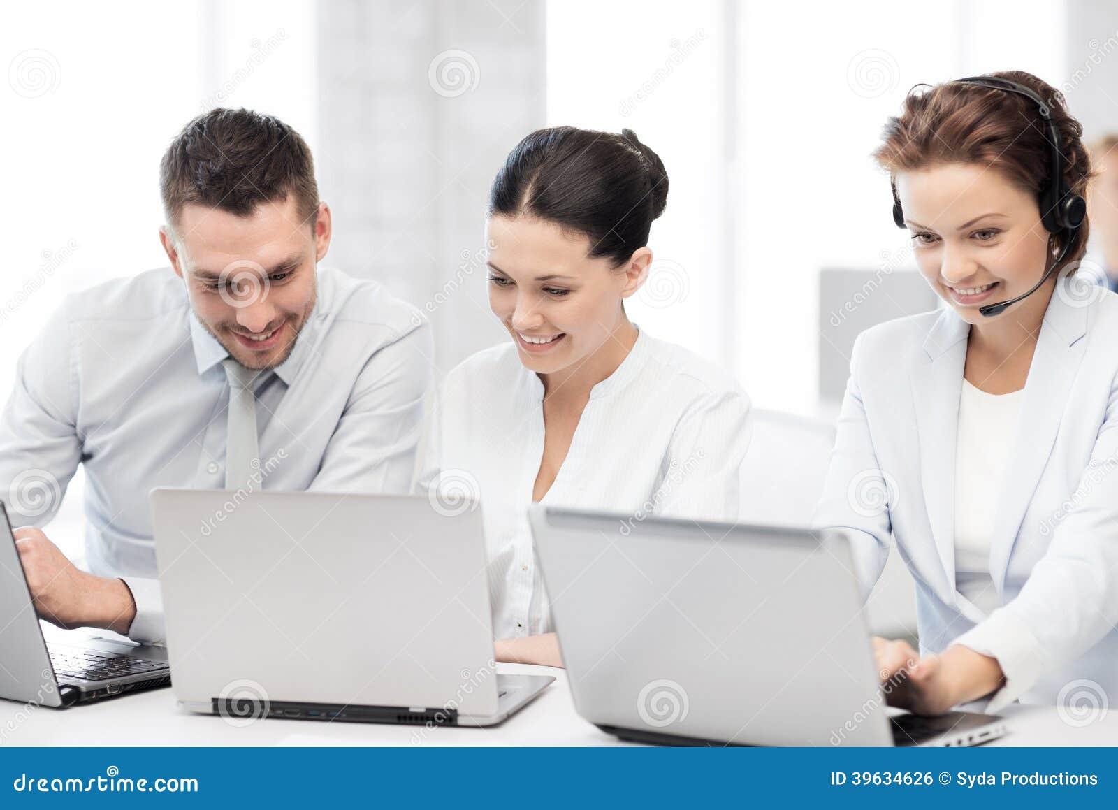Grupo de personas que trabaja con los ordenadores portátiles en oficina