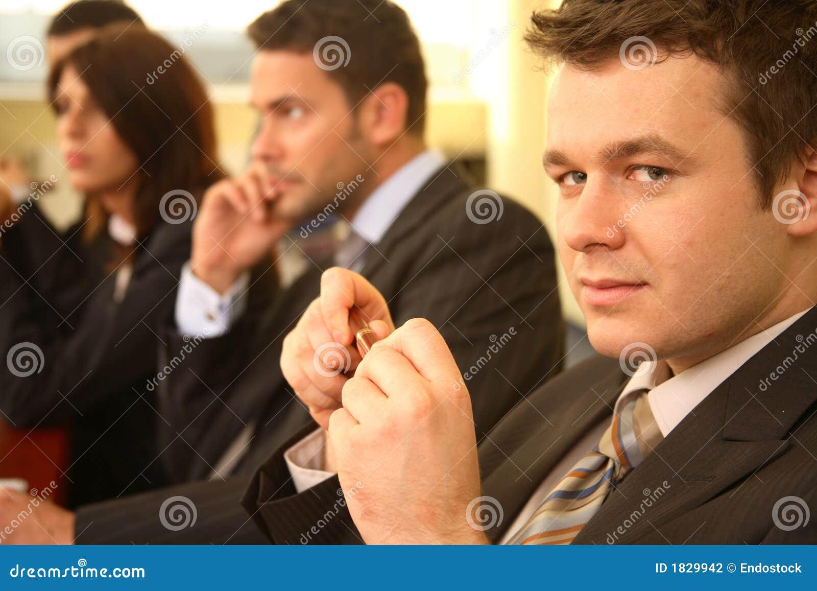 Grupo de pessoas do negócio em uma conferência, homem no foco