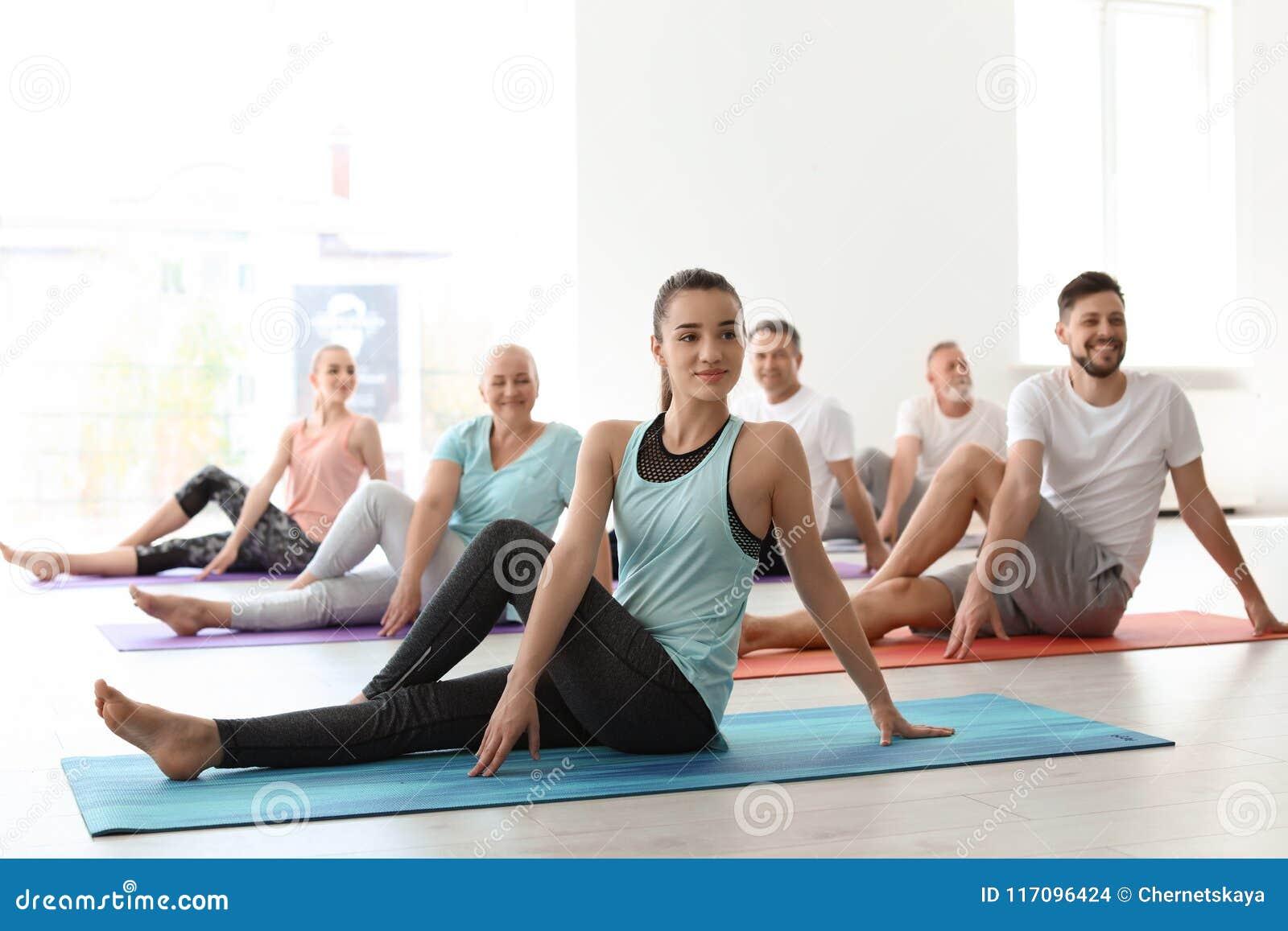 Grupo de pessoas na ioga praticando do sportswear