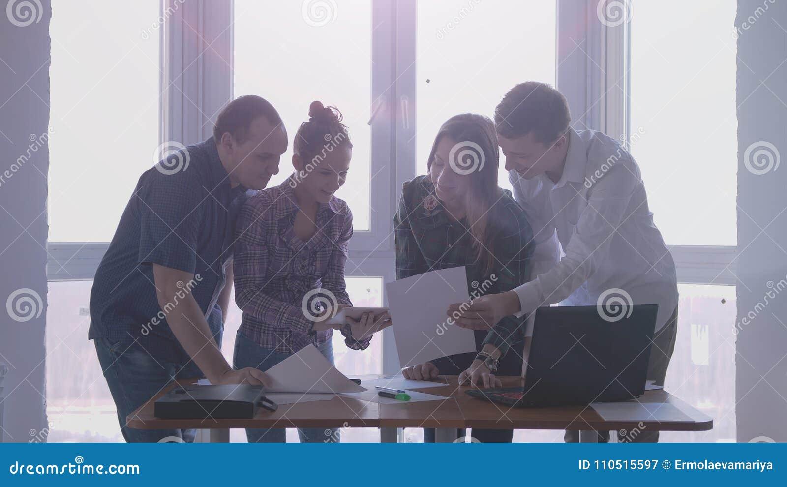 Grupo de pessoas no lugar de funcionamento durante a reunião incorporada em um escritório à moda com a grande janela panorâmico n