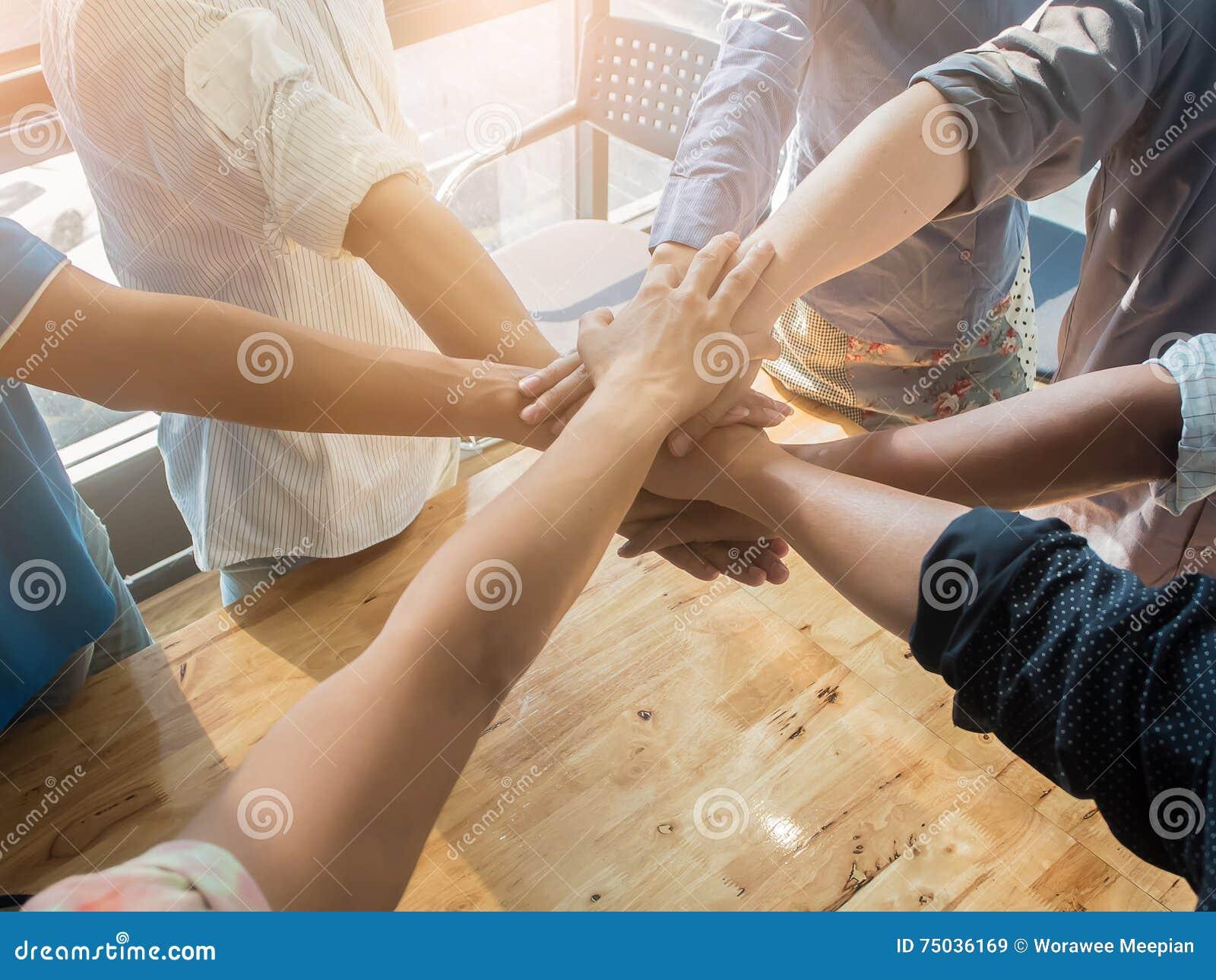 Grupo de pessoas que põe suas mãos que trabalham junto sobre o fundo de madeira no escritório conceito da cooperação dos trabalho