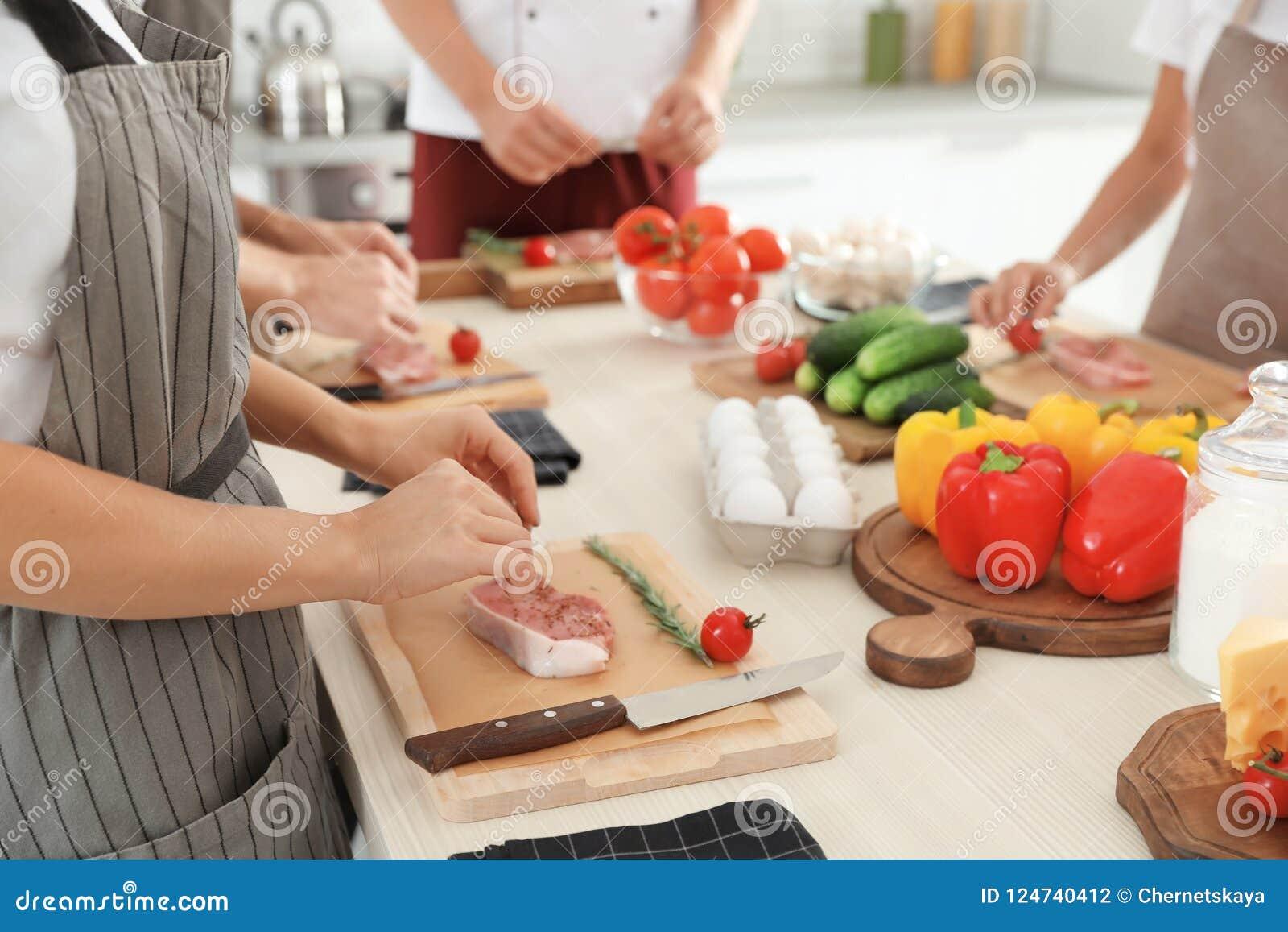 Grupo de pessoas que prepara a carne em aulas de culinária