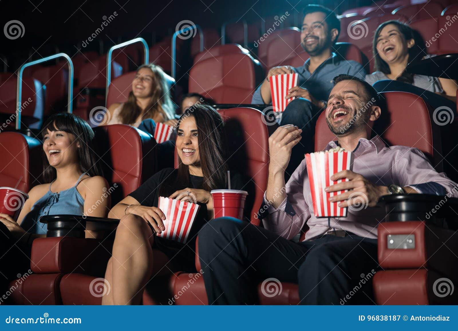 Grupo de pessoas que ri do cinema