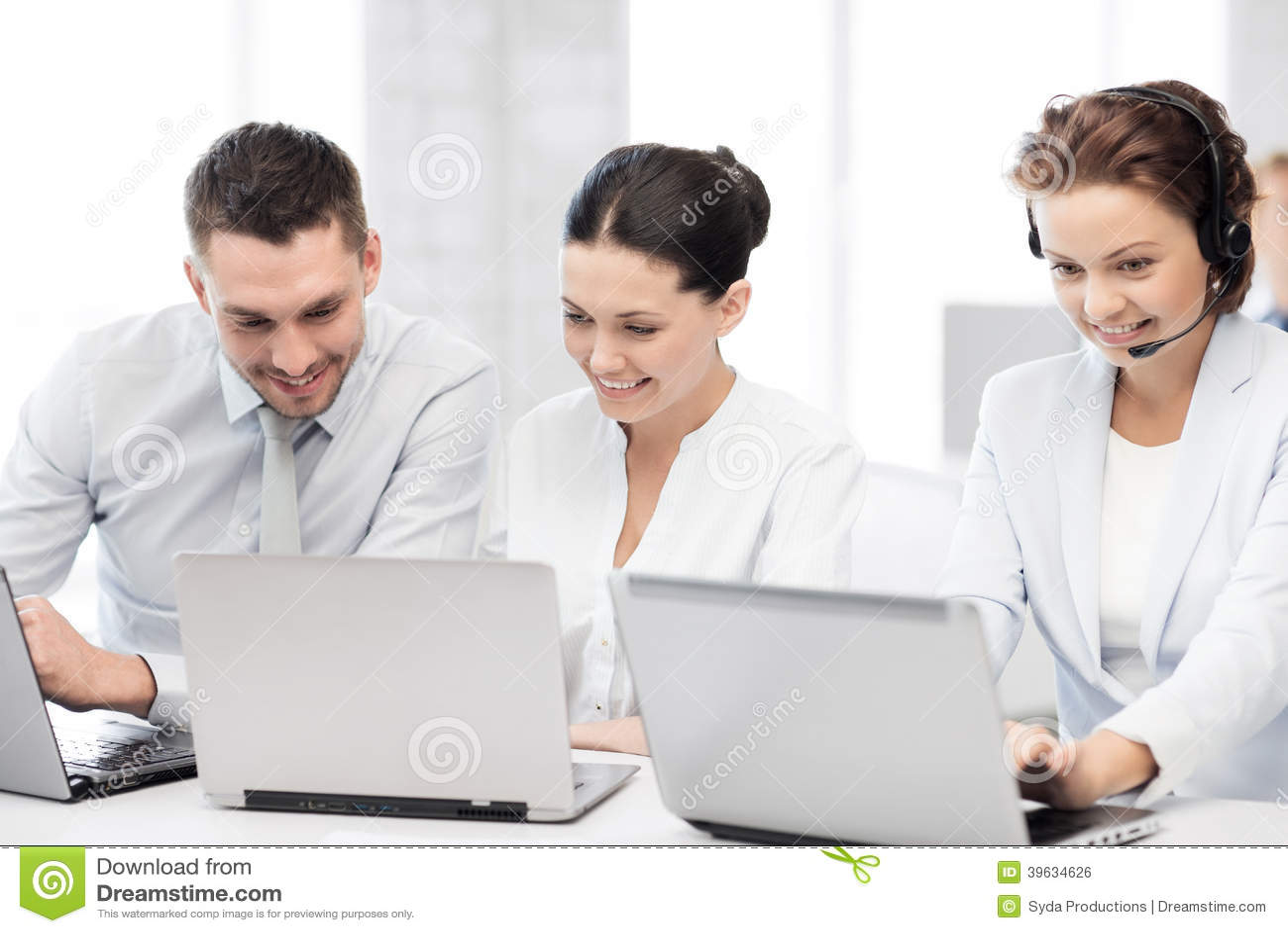 Grupo de pessoas que trabalha com os portáteis no escritório