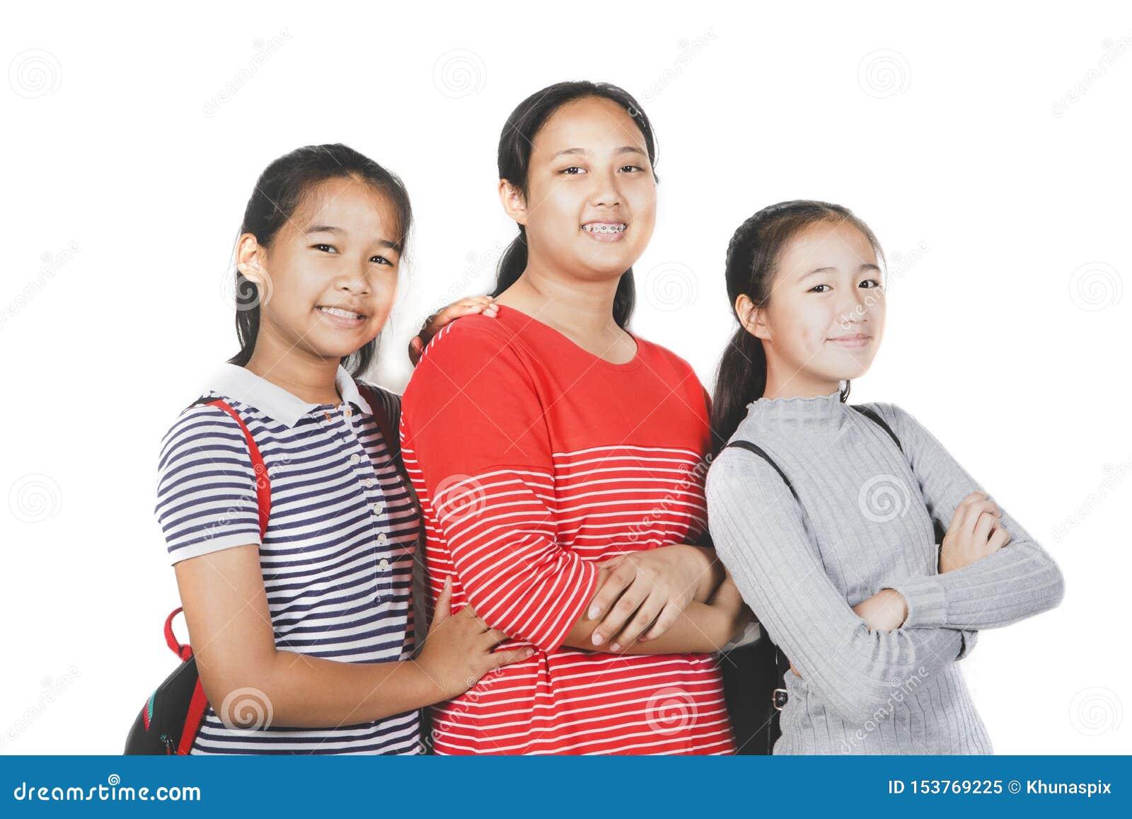 Grupo de posição de sorriso da cara do adolescente asiático contra o fundo branco