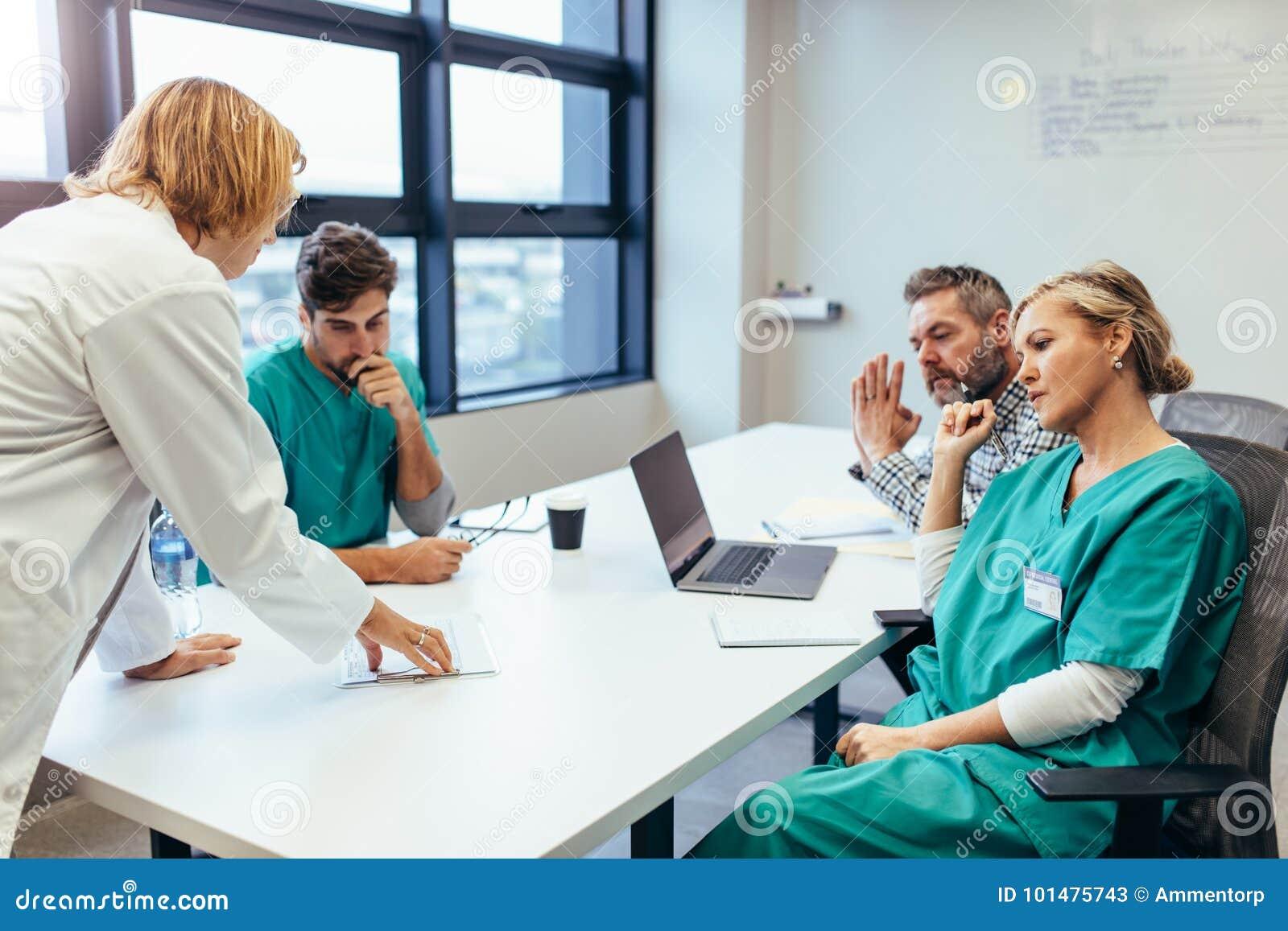 Grupo de profissionais médicos que conceituam na reunião