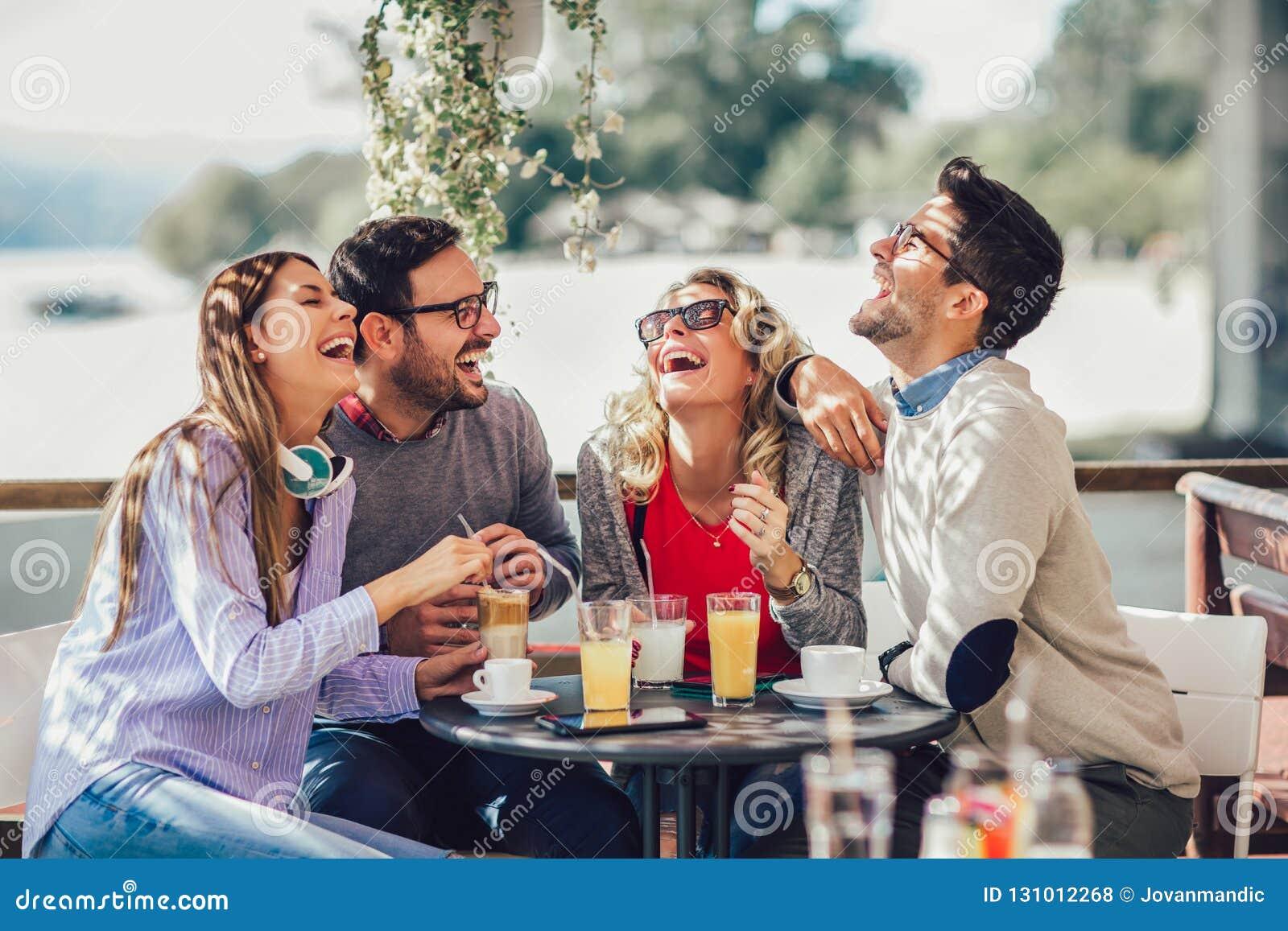 Grupo de quatro amigos que têm o divertimento um café junto