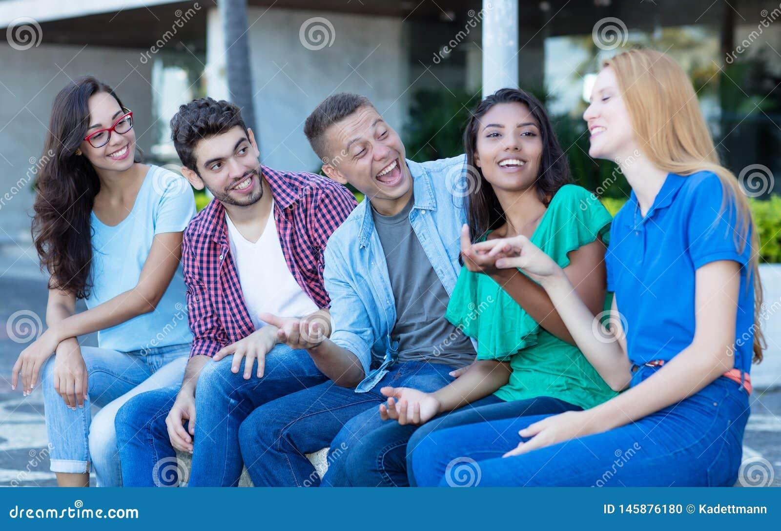 Grupo de rir homens e a mulher adultos novos