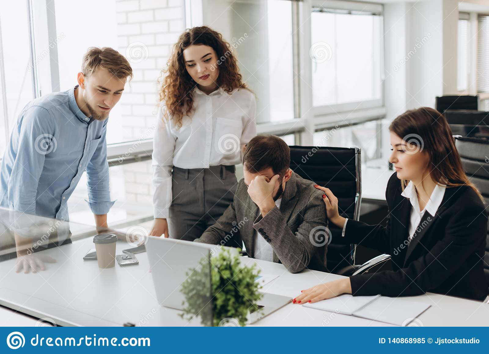 Grupo de sócios comerciais novos que trabalham no escritório moderno Colegas de trabalho que têm o problema ao trabalhar no portá