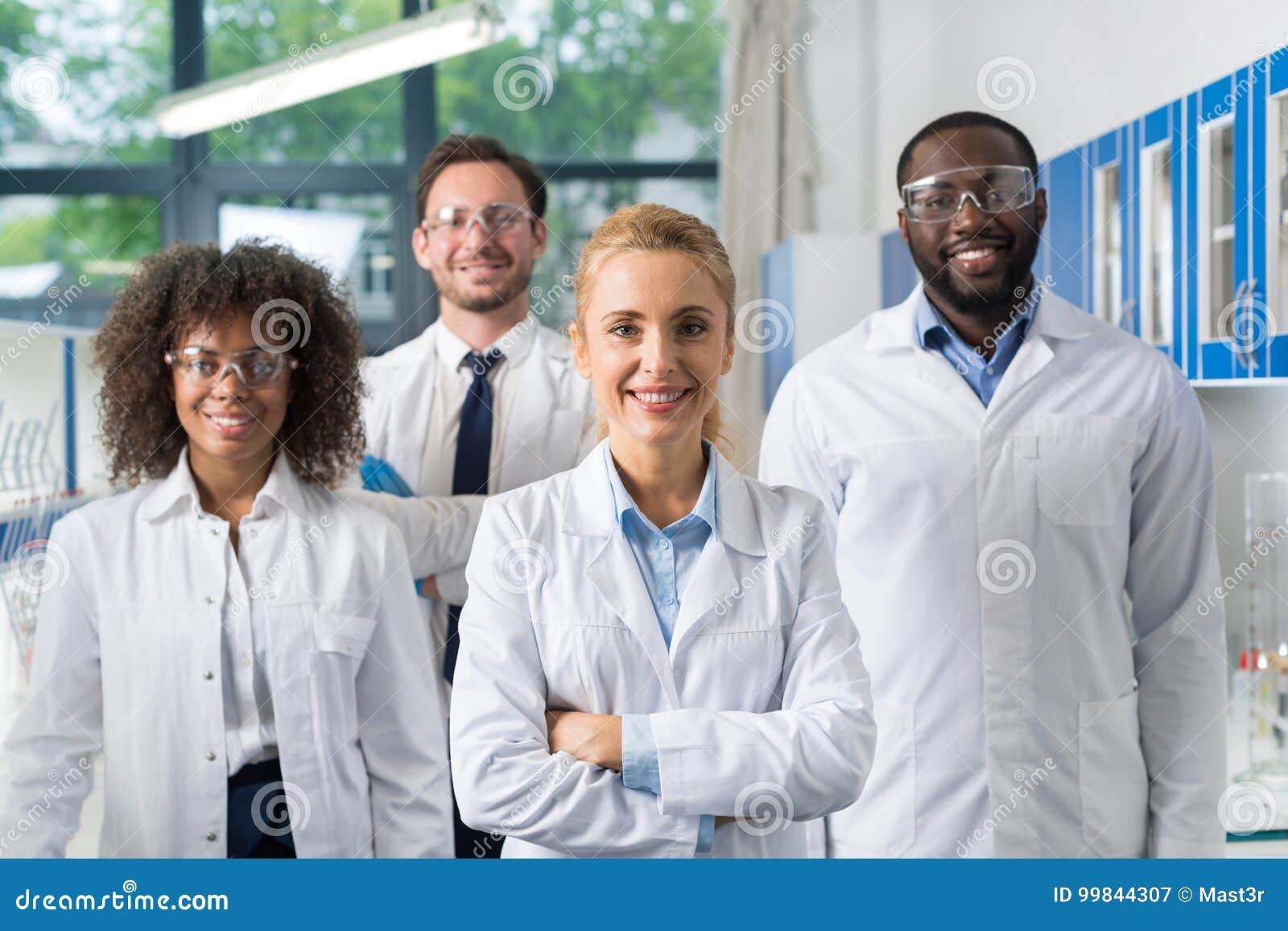 Grupo de sorriso de cientistas no laboratório moderno com líder fêmea, laboratório de Team Of Scientific Researchers In da raça d