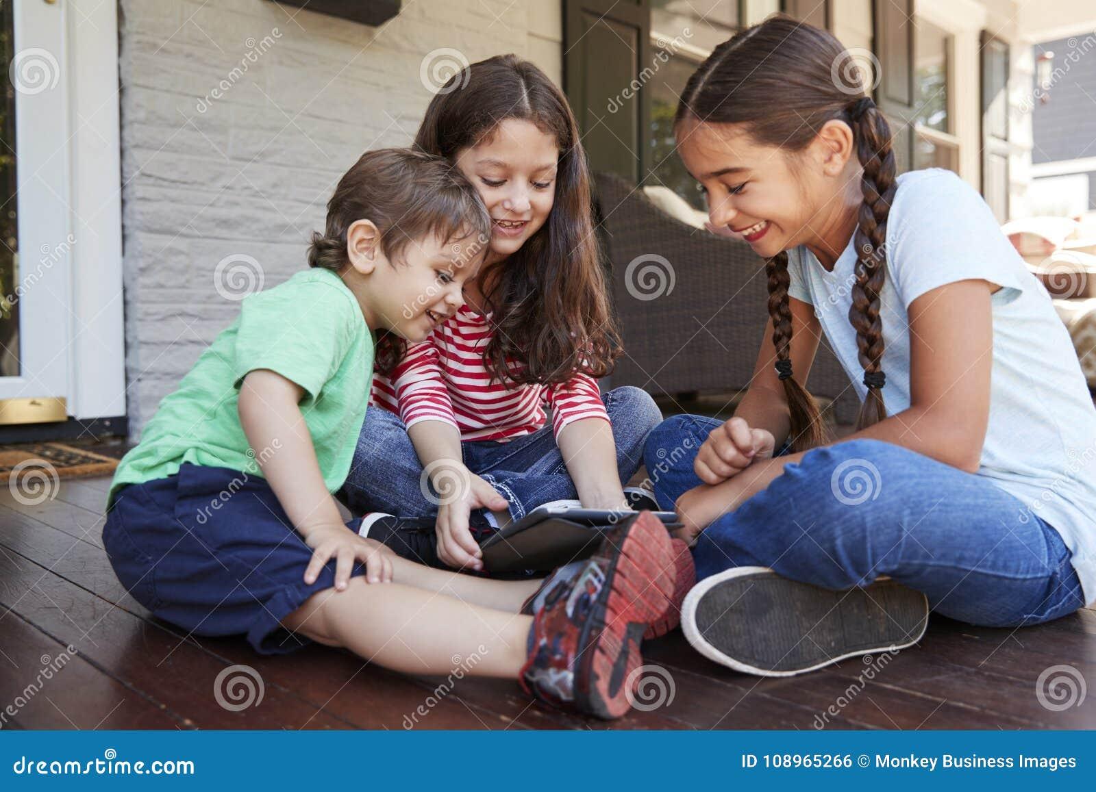 Grupo de tabuleta de Sit On Porch Playing With Digital das crianças
