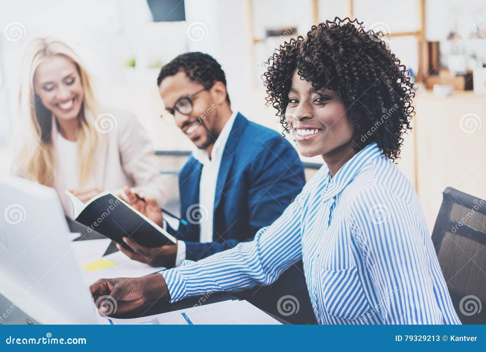 Grupo de três colegas de trabalho que trabalham junto no projeto do negócio no escritório moderno Mulher africana atrativa nova q