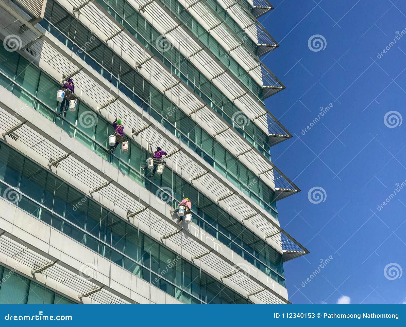 Grupo de trabajadores que limpian servicio de las ventanas en el alto edificio