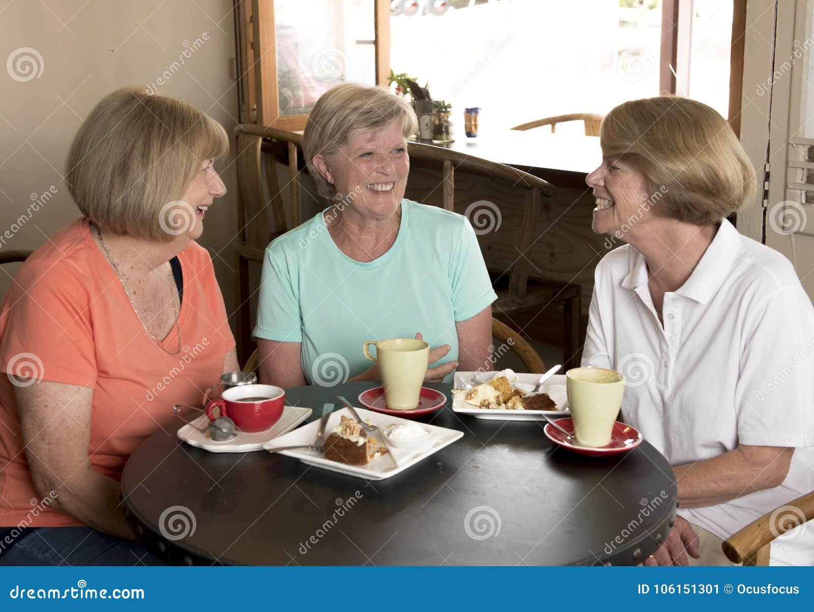 Grupo de tres novias maduras mayores de las mujeres de la Edad Media preciosa que se encuentran para el café y el té con las tort