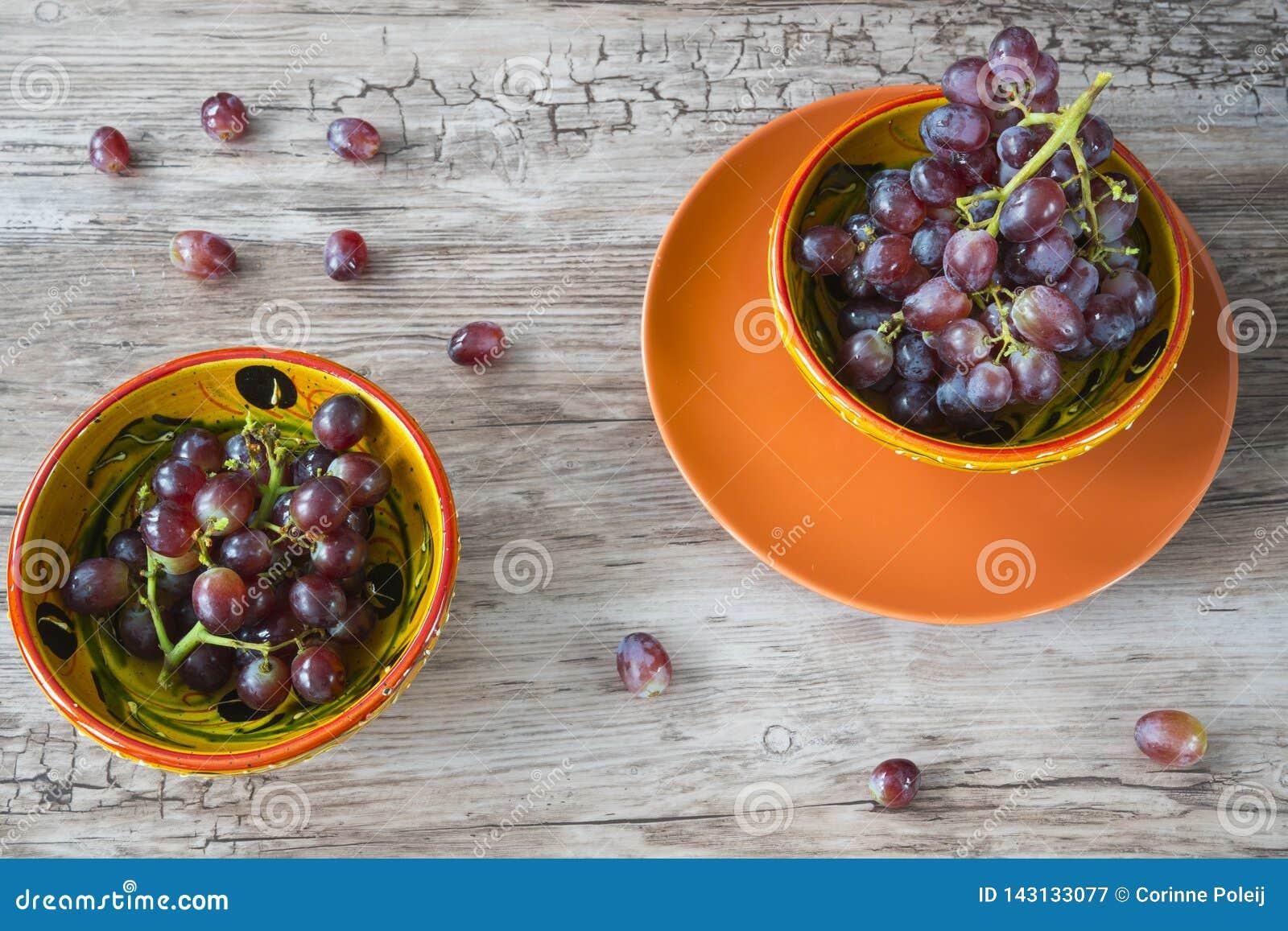 Grupo de uvas vermelhas na bacia alaranjada, contra o fundo de madeira
