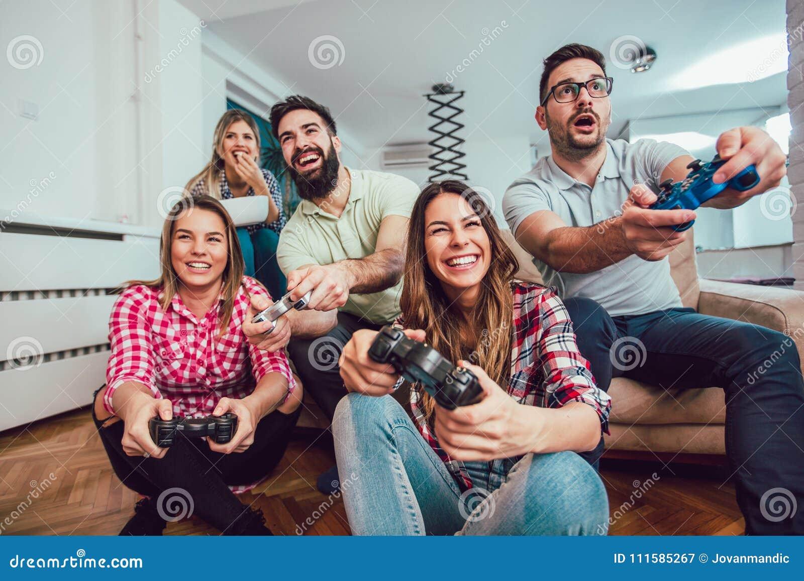 Grupo De Videojuegos Del Juego De Los Amigos Junto En Casa Imagen De