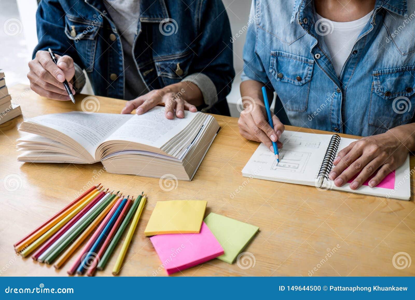 Grupo del profesor particular o de estudiante universitario de la escuela secundaria que se sienta en el escritorio en la bibliot