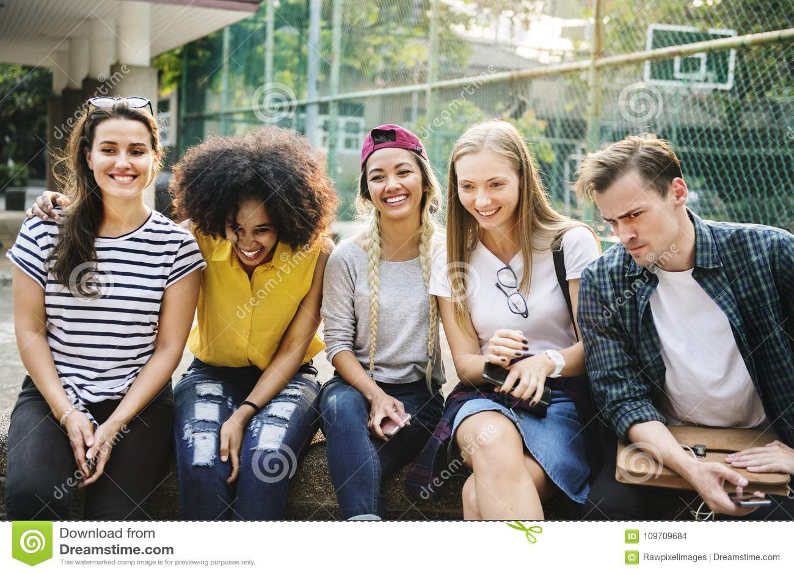 Grupo diverso de amigos que penduram para fora nos millennials do parque e no conceito da cultura de juventude