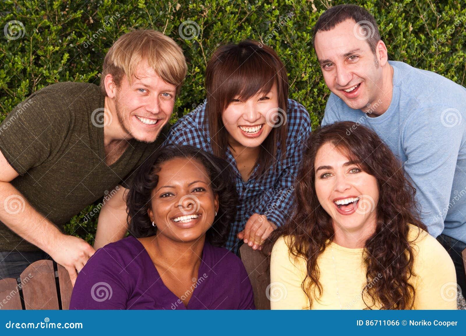 Grupo diverso de amigos que se sientan afuera