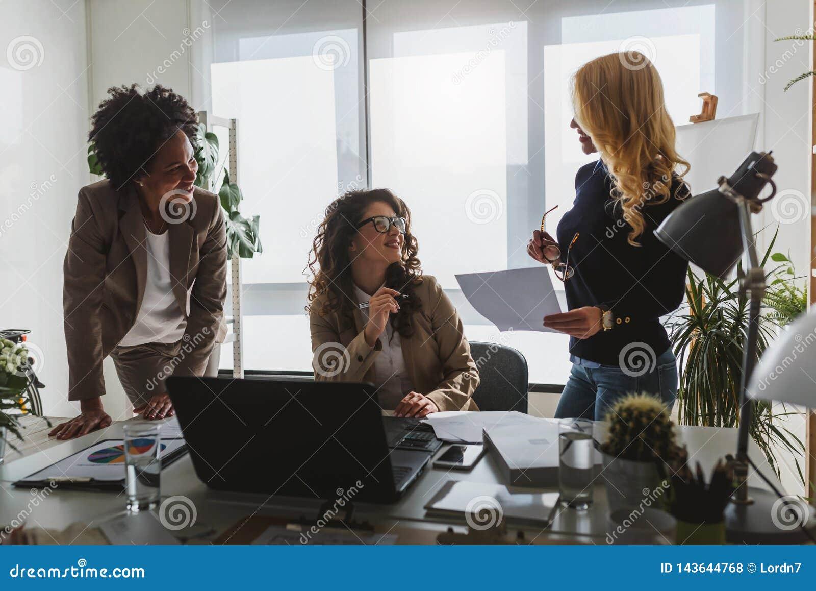 Grupo diverso de mujeres de negocios sonrientes que tienen una rotura en hablar de la oficina